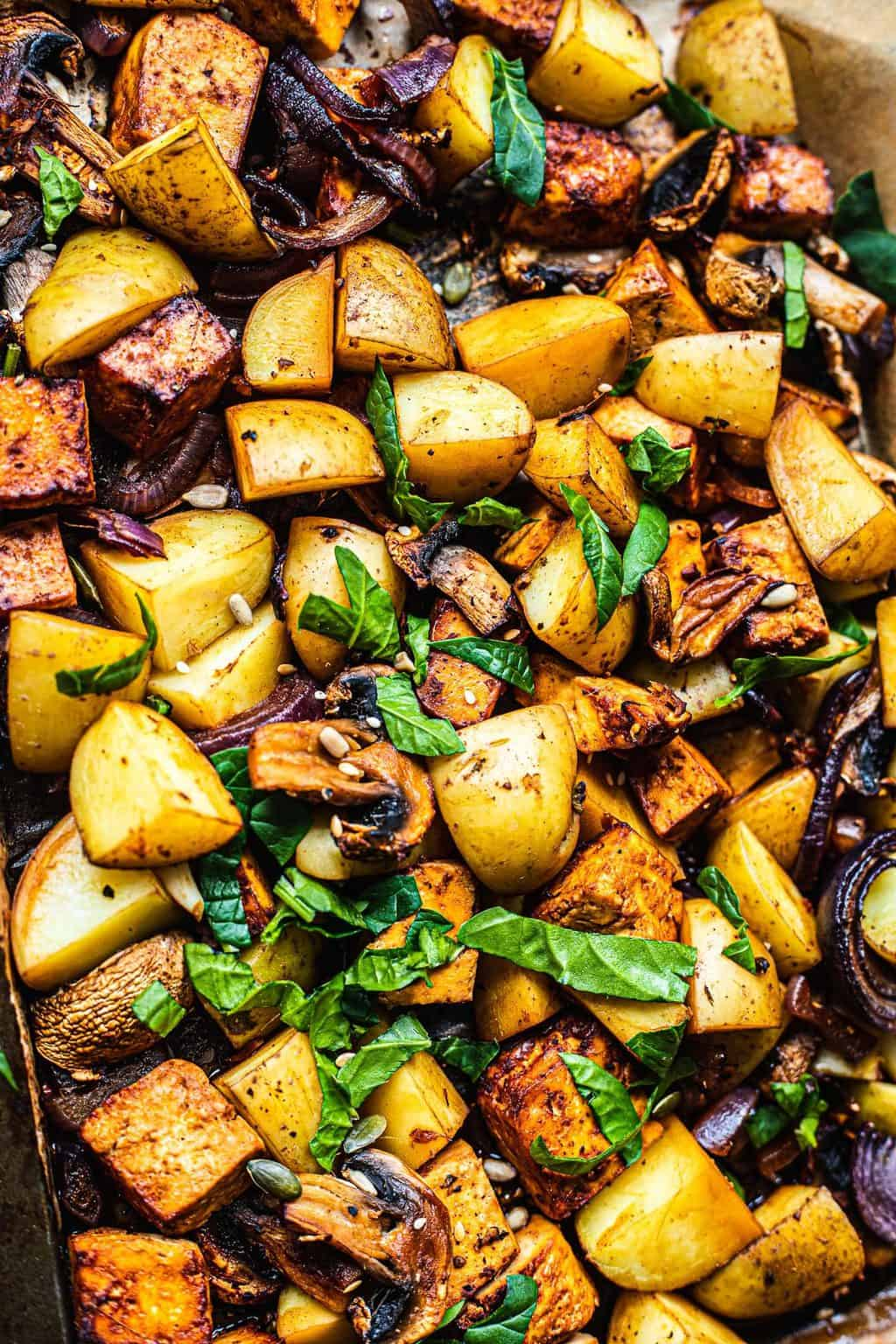 Potatoes tofu and mushrooms on a baking tray