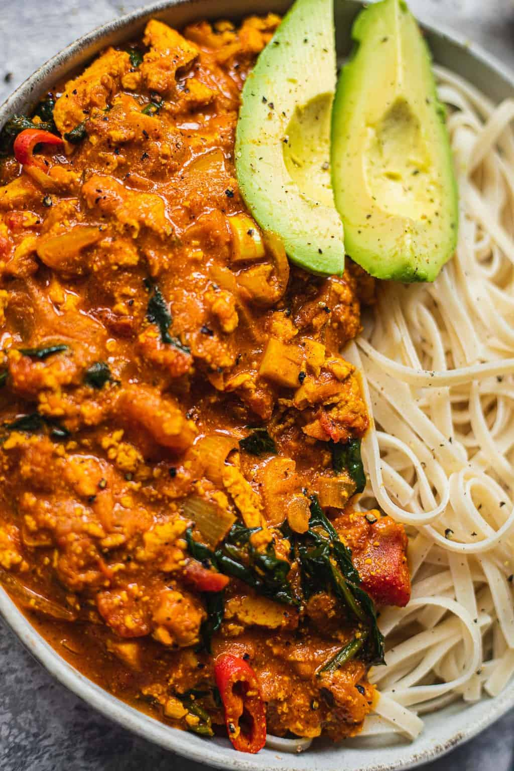 Closeup of vegan curry with noodles and avocado