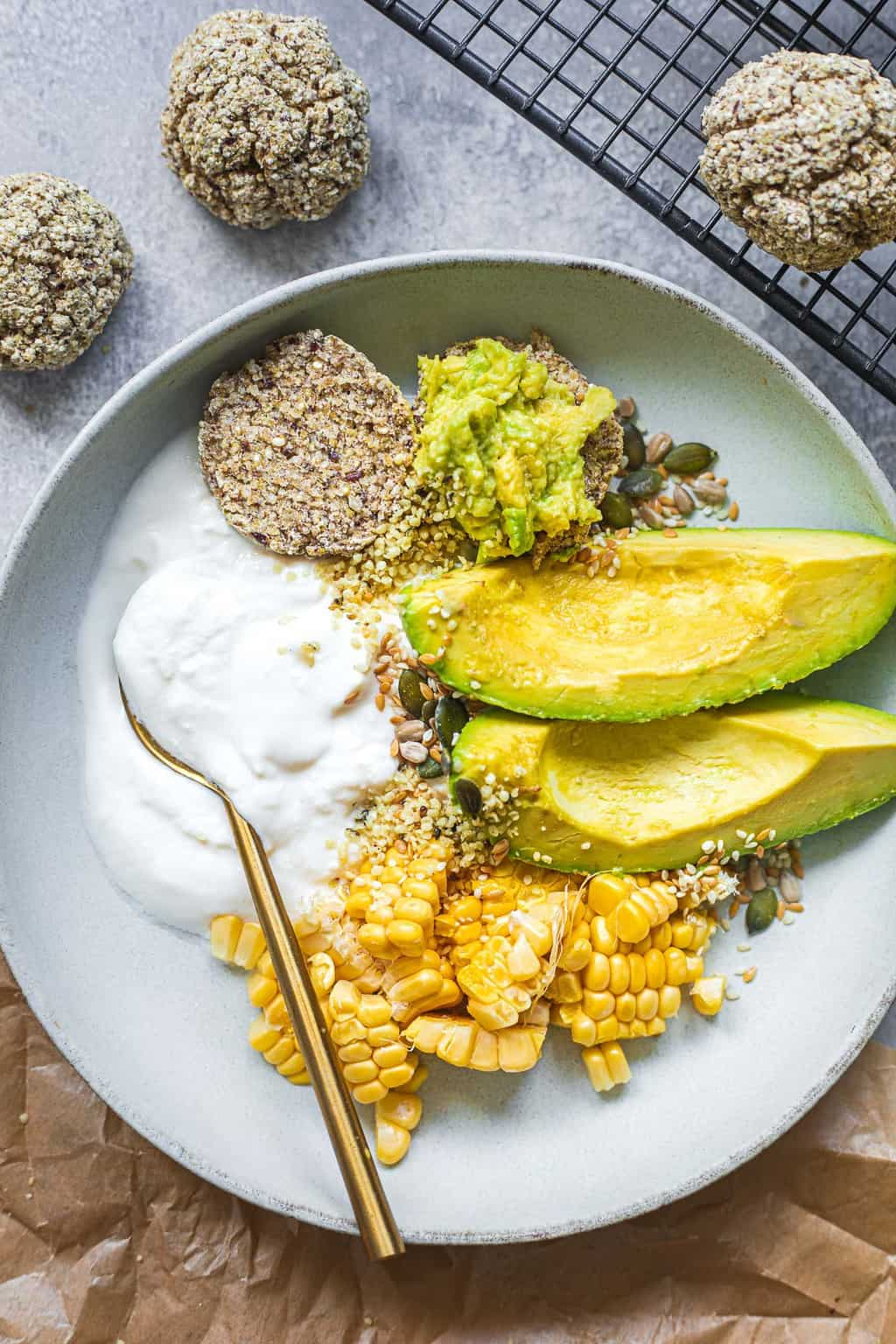 Vegan breakfast bowl with bread rolls, soy yoghurt and avocado
