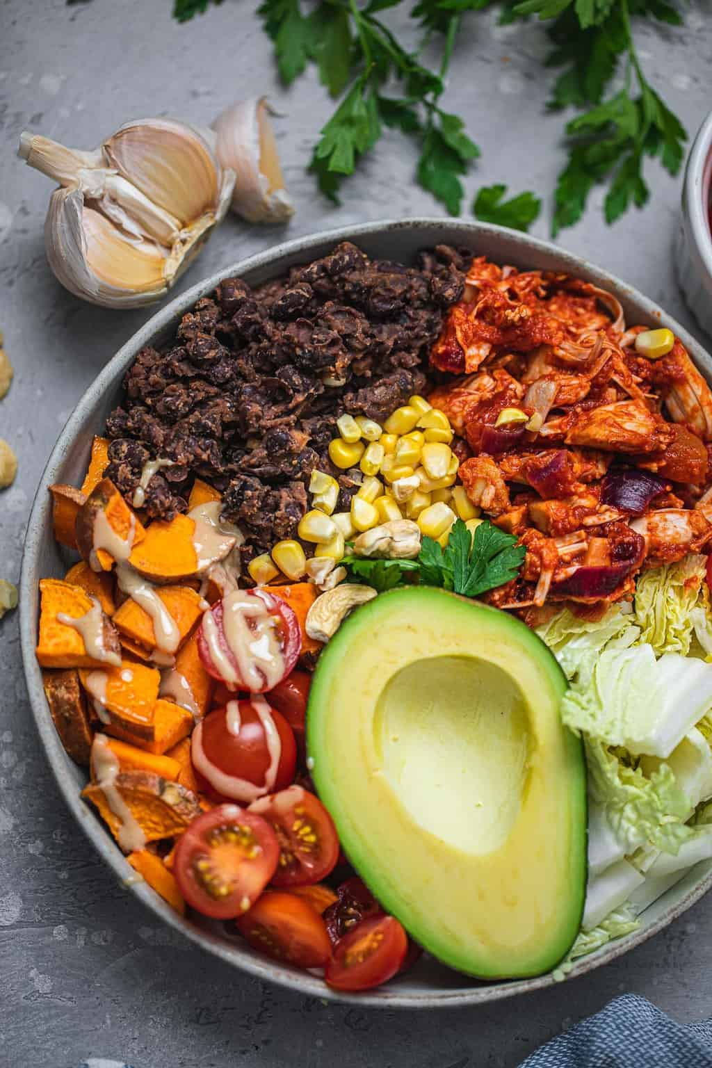 Bowl with black beans, sweet potato, lettuce, avocado, sweetcorn and tahini