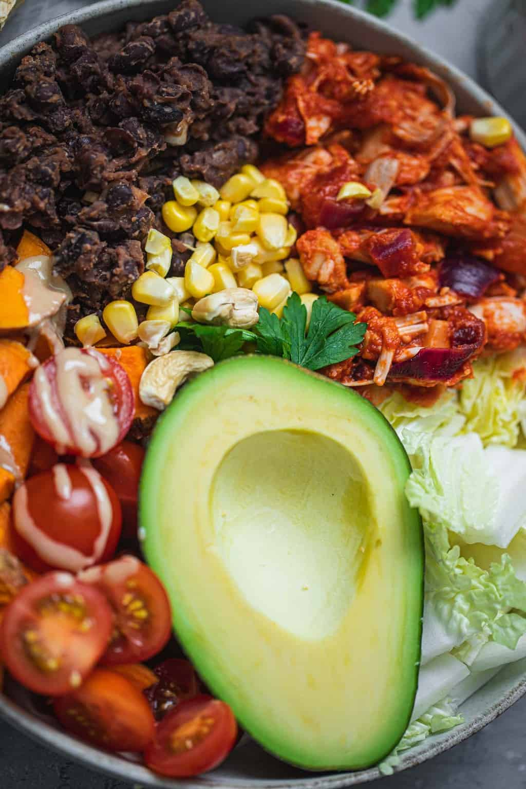Burrito bowl with avocado, sweetcorn, jackfruit, lettuce tomatoes, refried beans and tahini