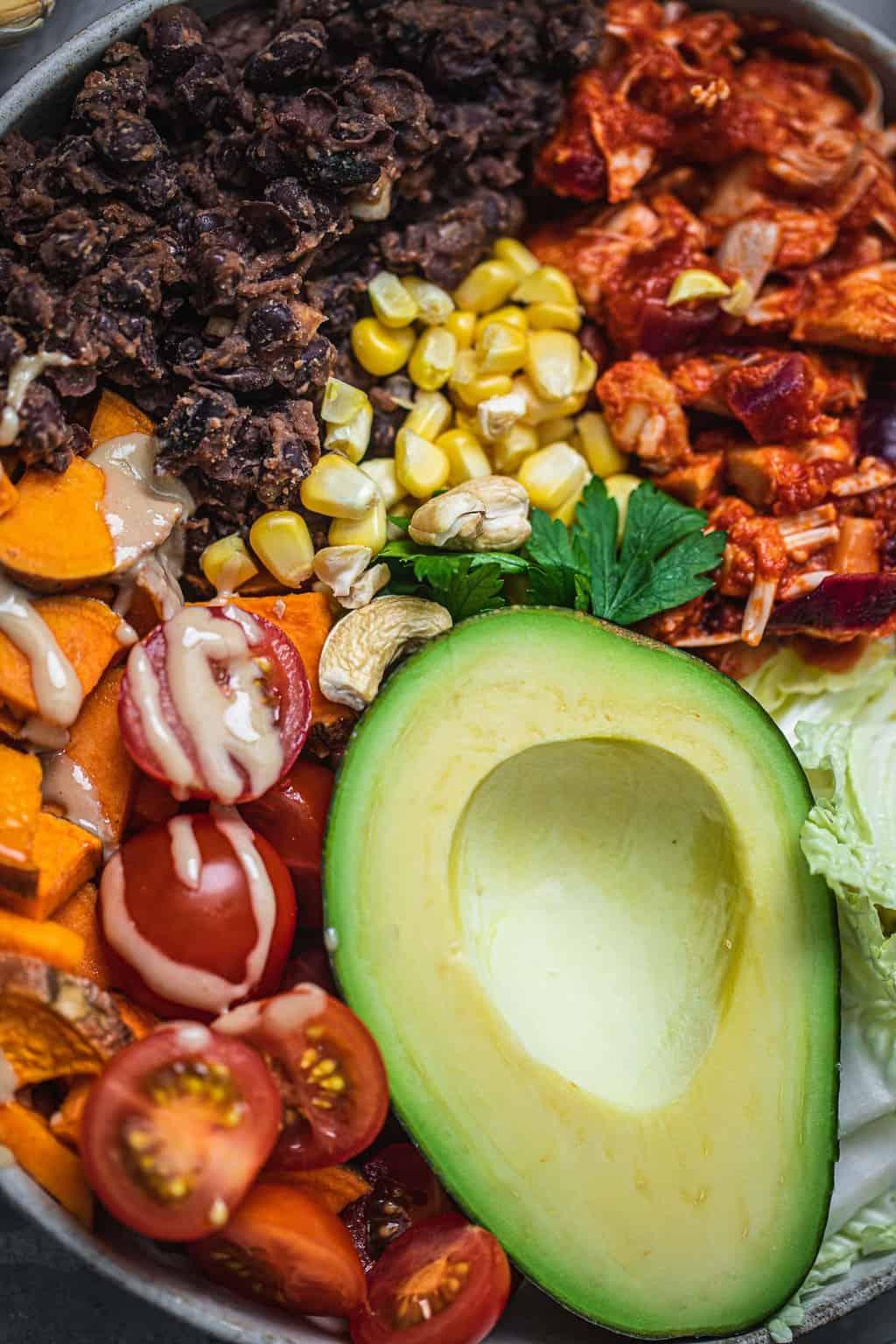 Closeup of a vegan bowl with black beans, jackfruit, sweet potato and avocado
