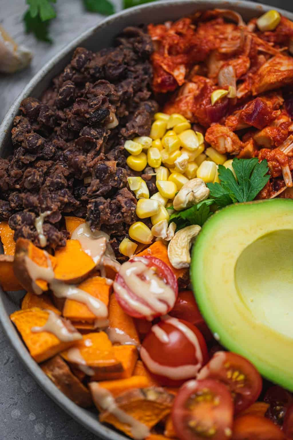 Closeup of a bowl with black beans, jackfruit, sweet potatoes, avocado and corn