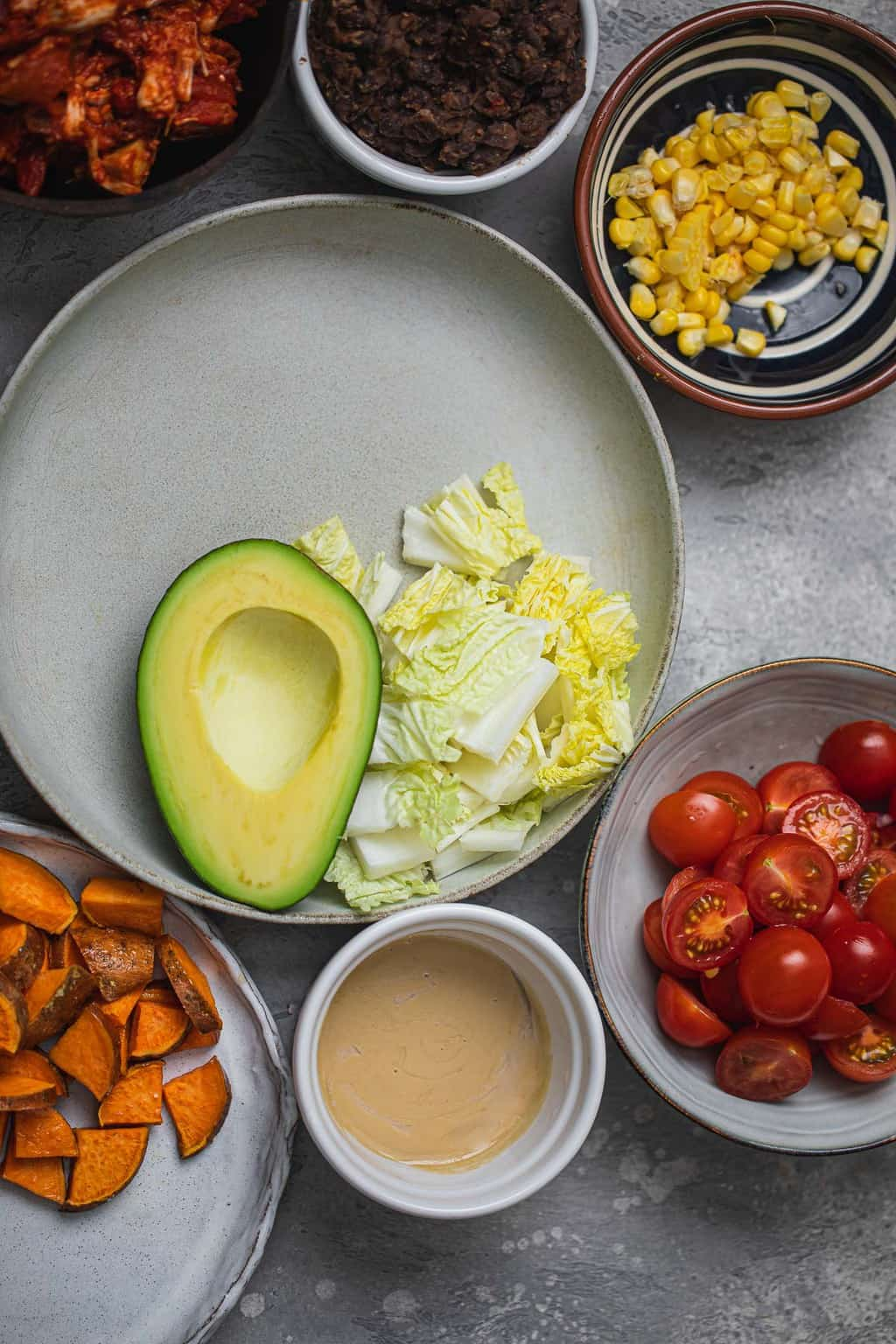 Bowl with avocado and lettuce surrounded by jackfruit, tomatoes, sweet potatoes, tahini, sweetcorn, and black beans