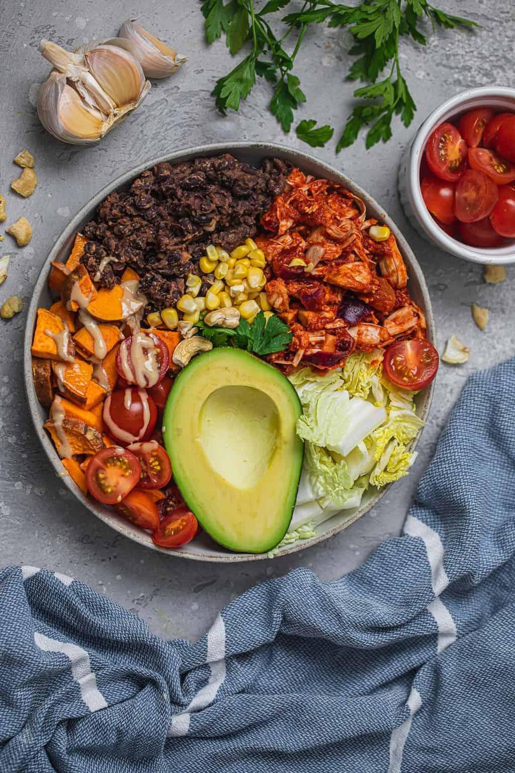Breakfast burrito bowl with refried beans, smoky jackfruit, sweet potatoes, tomatoes, avocado and tahini