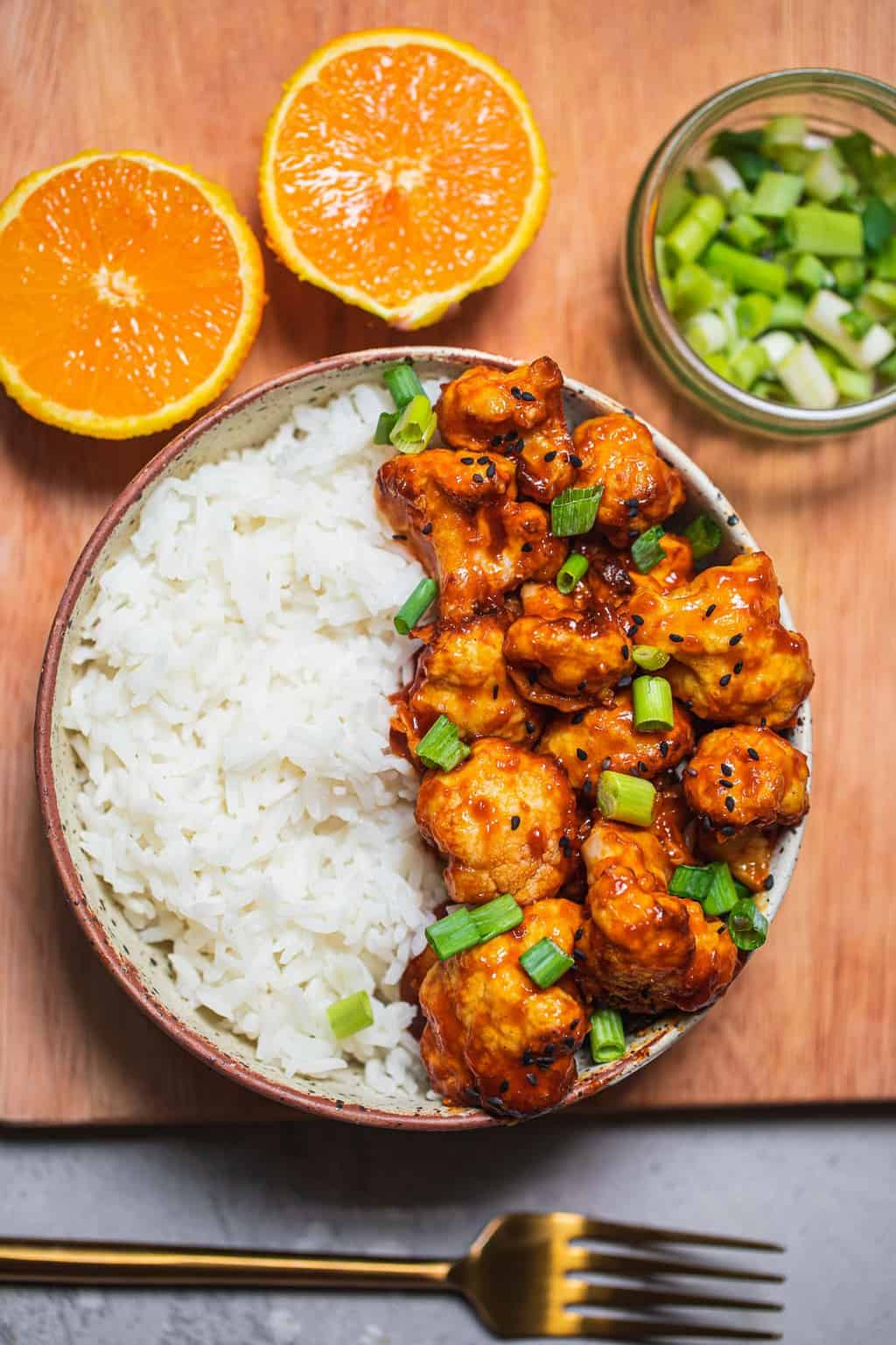 Bowl with orange cauliflower resting on a bed of rice