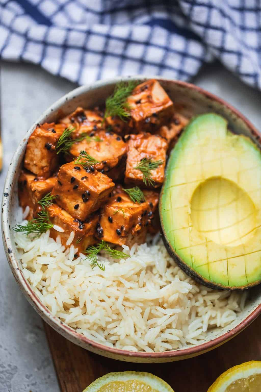 Tofu in a sesame peanut tofu and avocado over a bed of rice