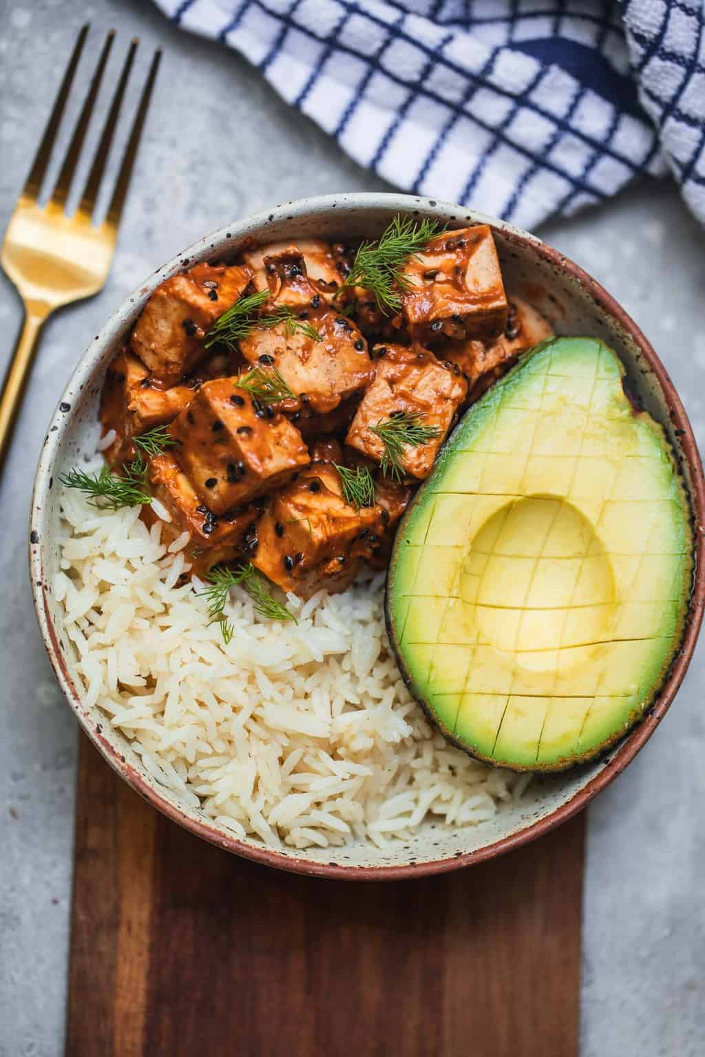 Bowl with tofu, avocado and rice on a chopping board