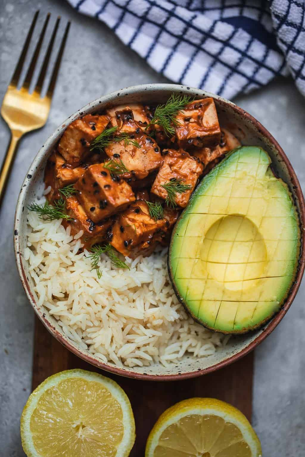 Sesame peanut tofu over a bed of rice with avocado