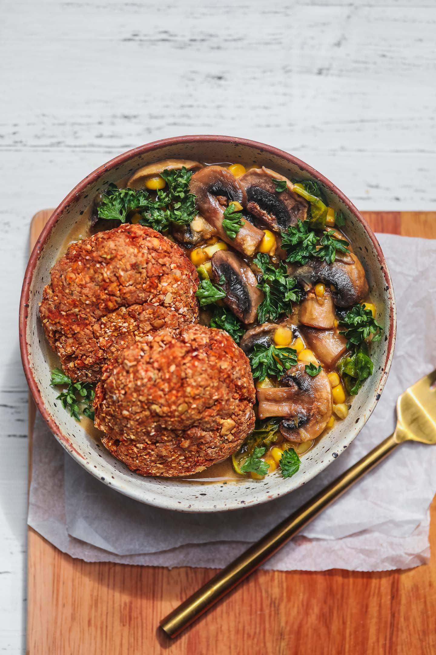 Bowl of vegan lentil burgers over a kale and mushroom stew
