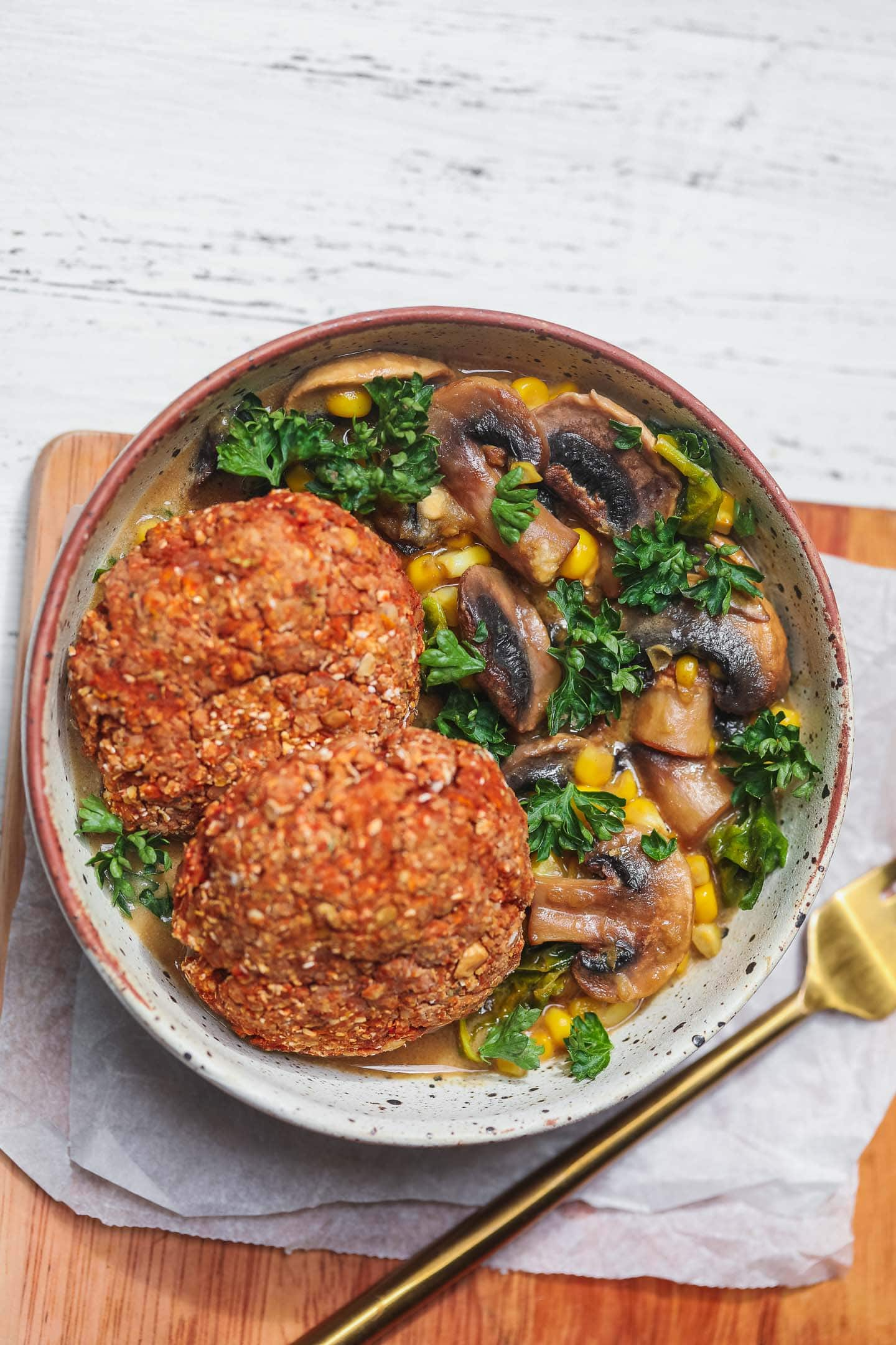 Bowl with vegan burgers over a mushroom and kale stew