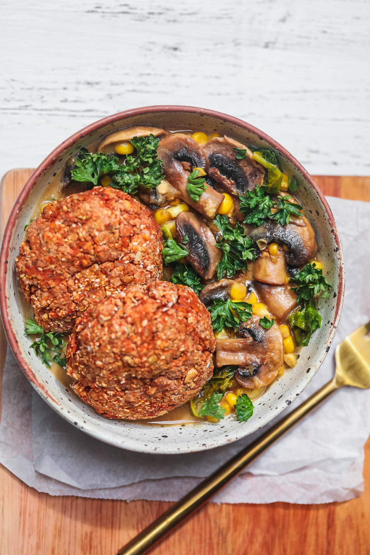 Vegan lentil burgers over a bowl of mushroom stew