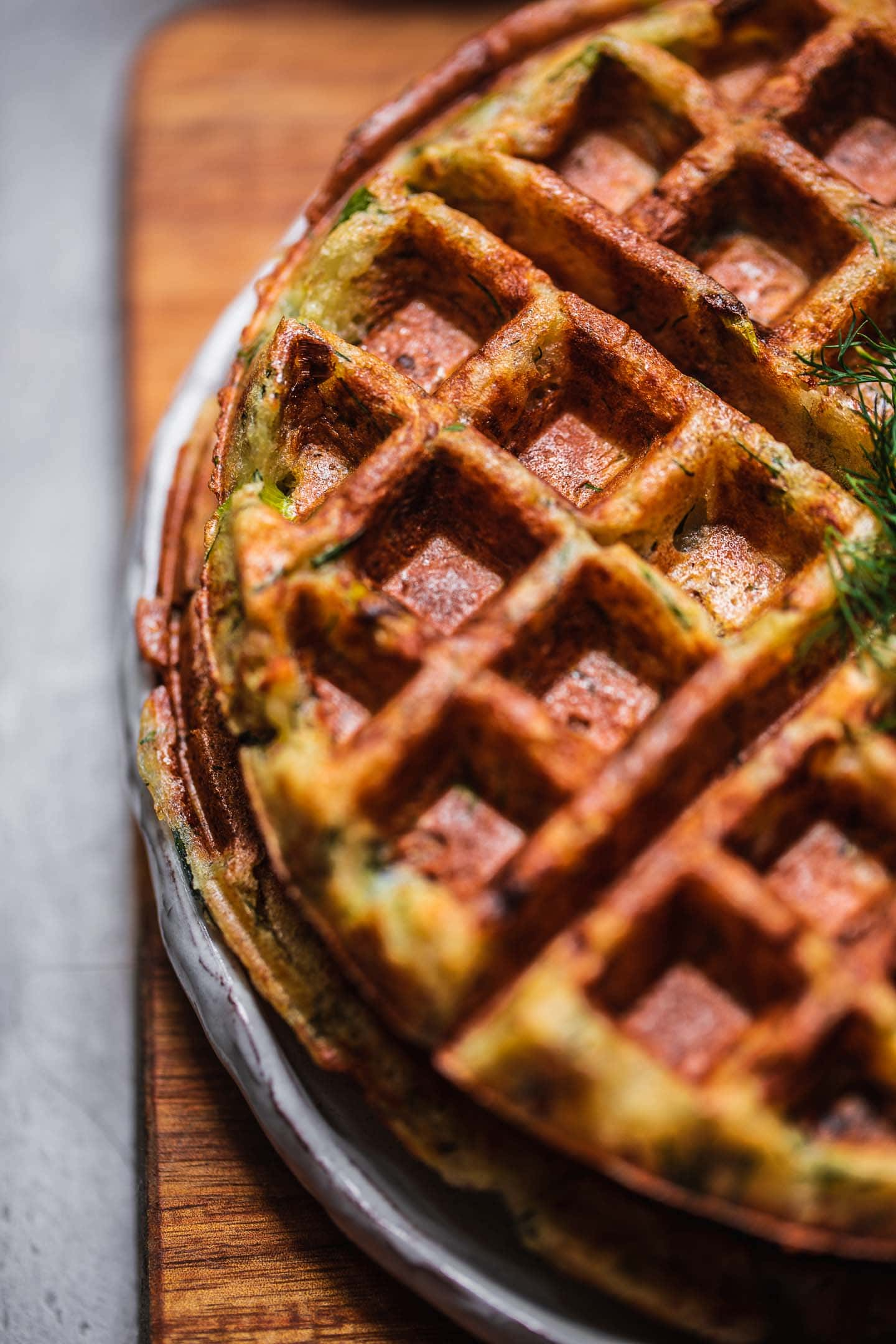 Closeup of potato waffles on a white plate and a chopping board