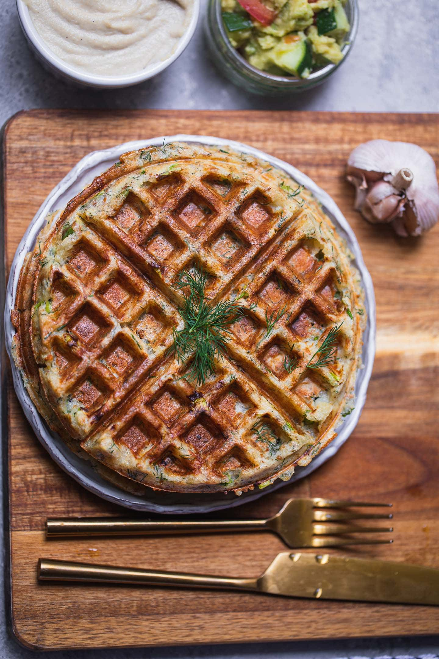 Vegan potato waffle on a white plate and a chopping board with a knife and fork nearby