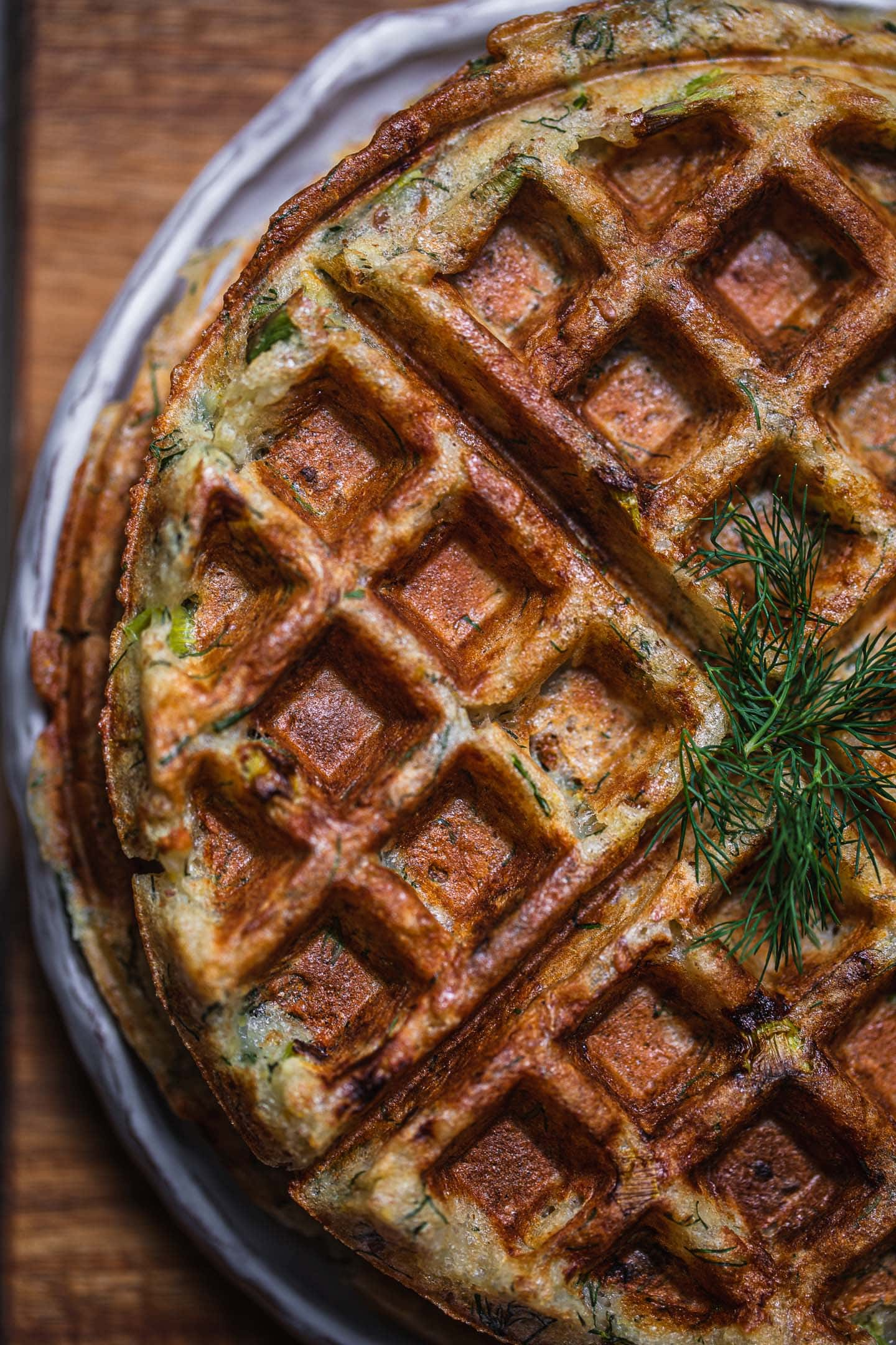 Pile of waffles with dill on a white plate and chopping board