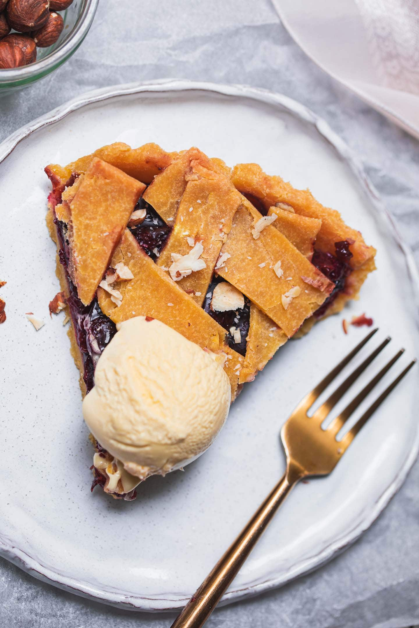 Slice of gluten-free vegan cherry pie with dairy-free ice cream