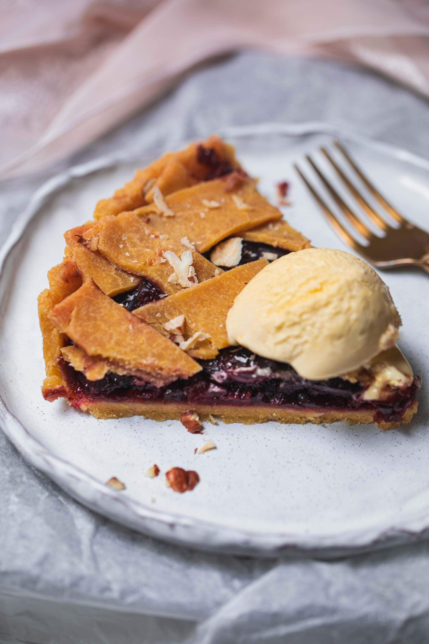 Slice of vegan pie with a cherry filling and dairy-free ice cream