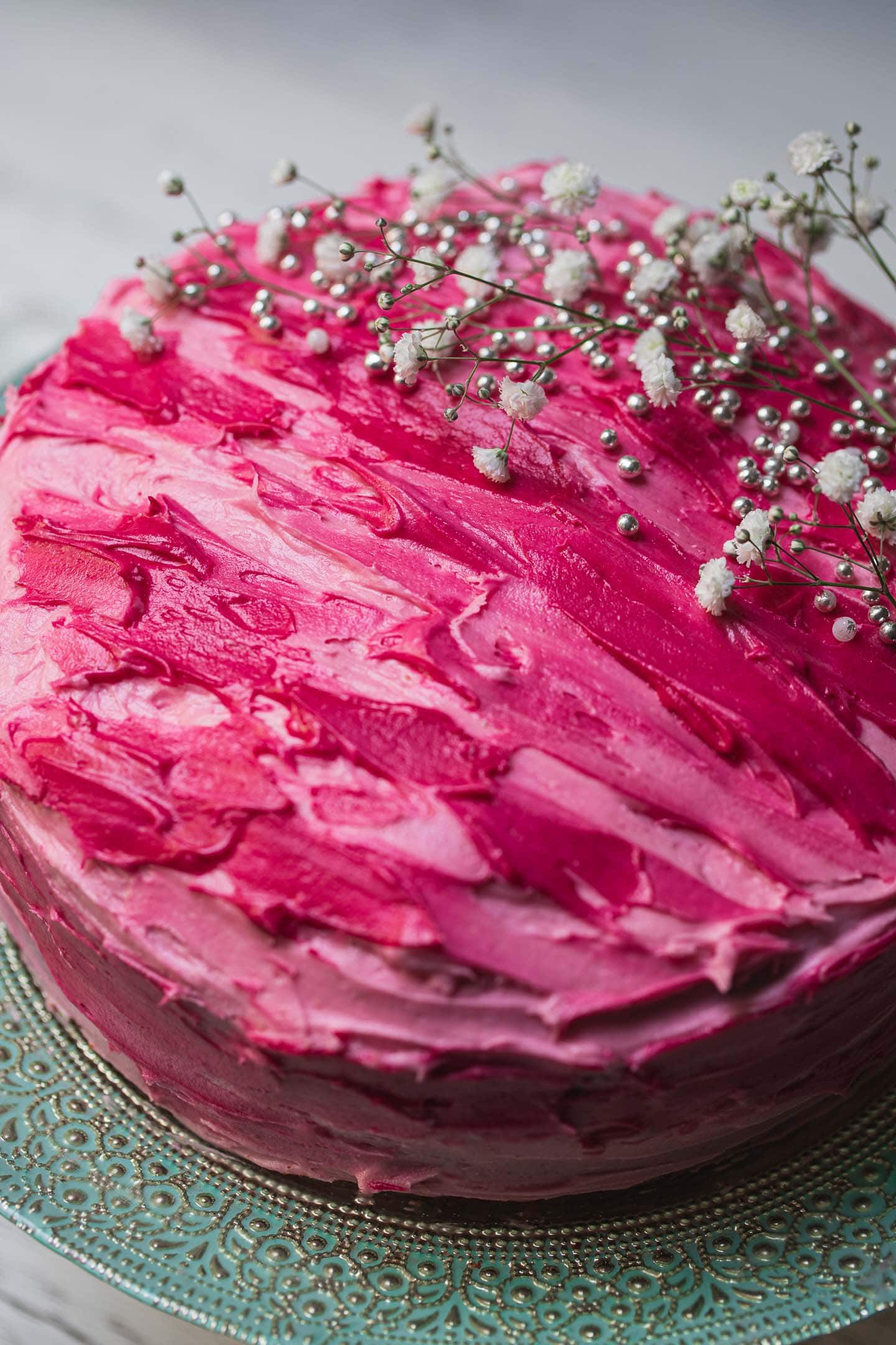 Closeup of a vegan vanilla cake with bright pink frosting