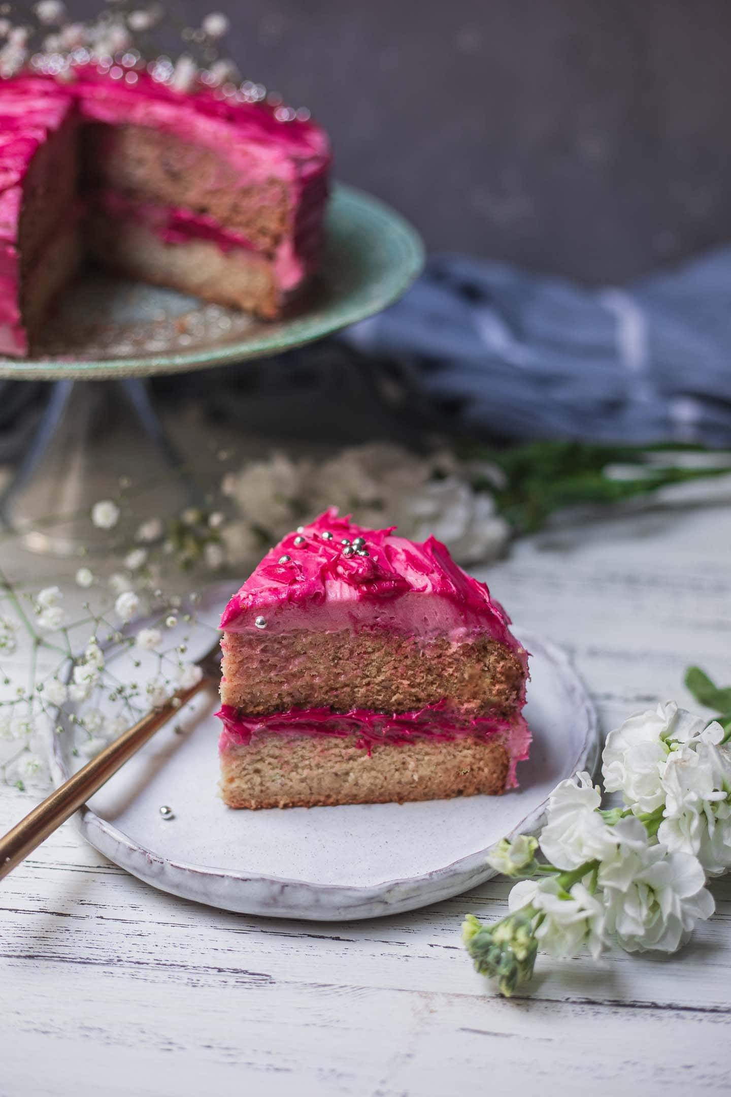 Slice of vegan vanilla cake with bright pink frosting