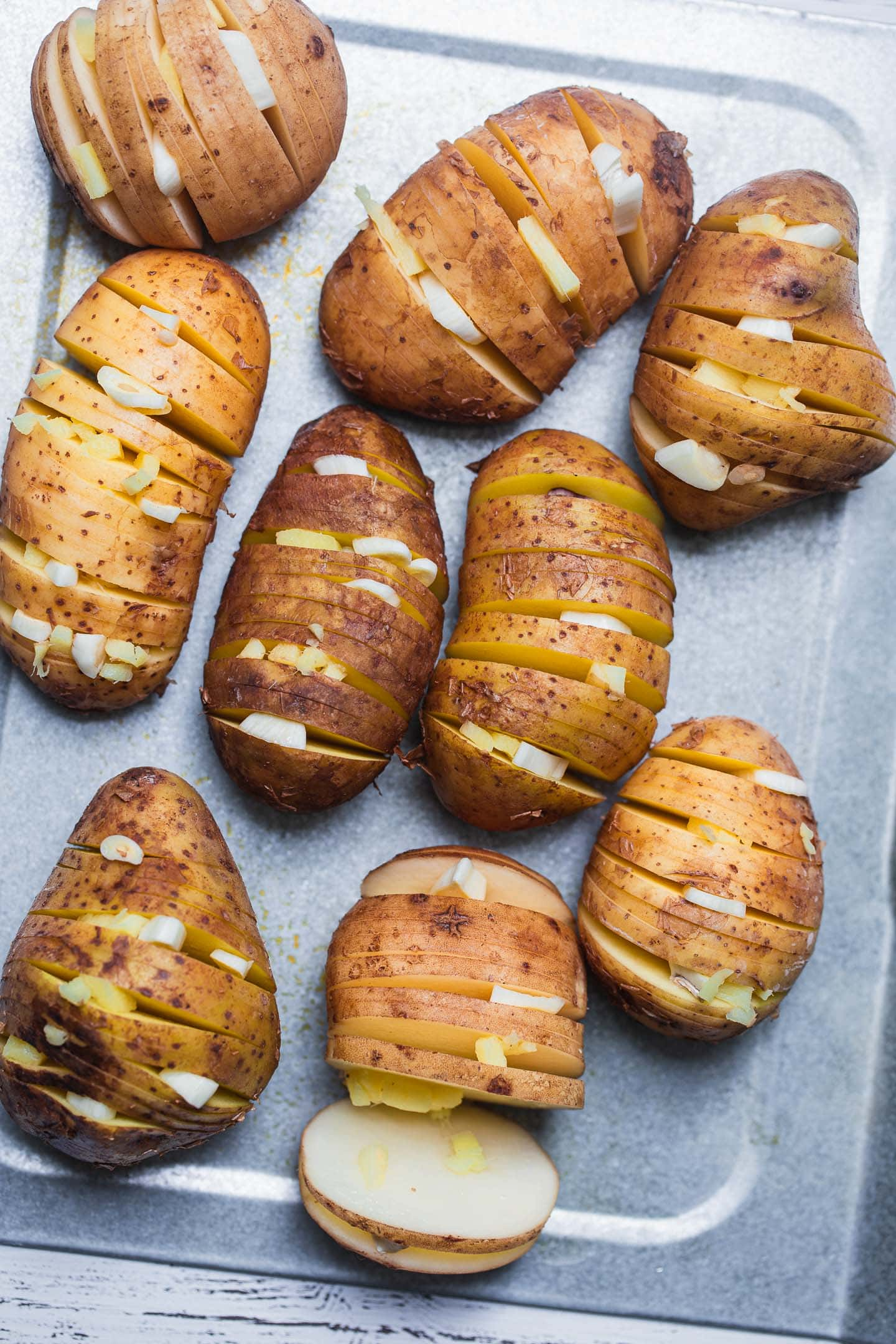 Hasselback potatoes with garlic and ginger on a baking tray