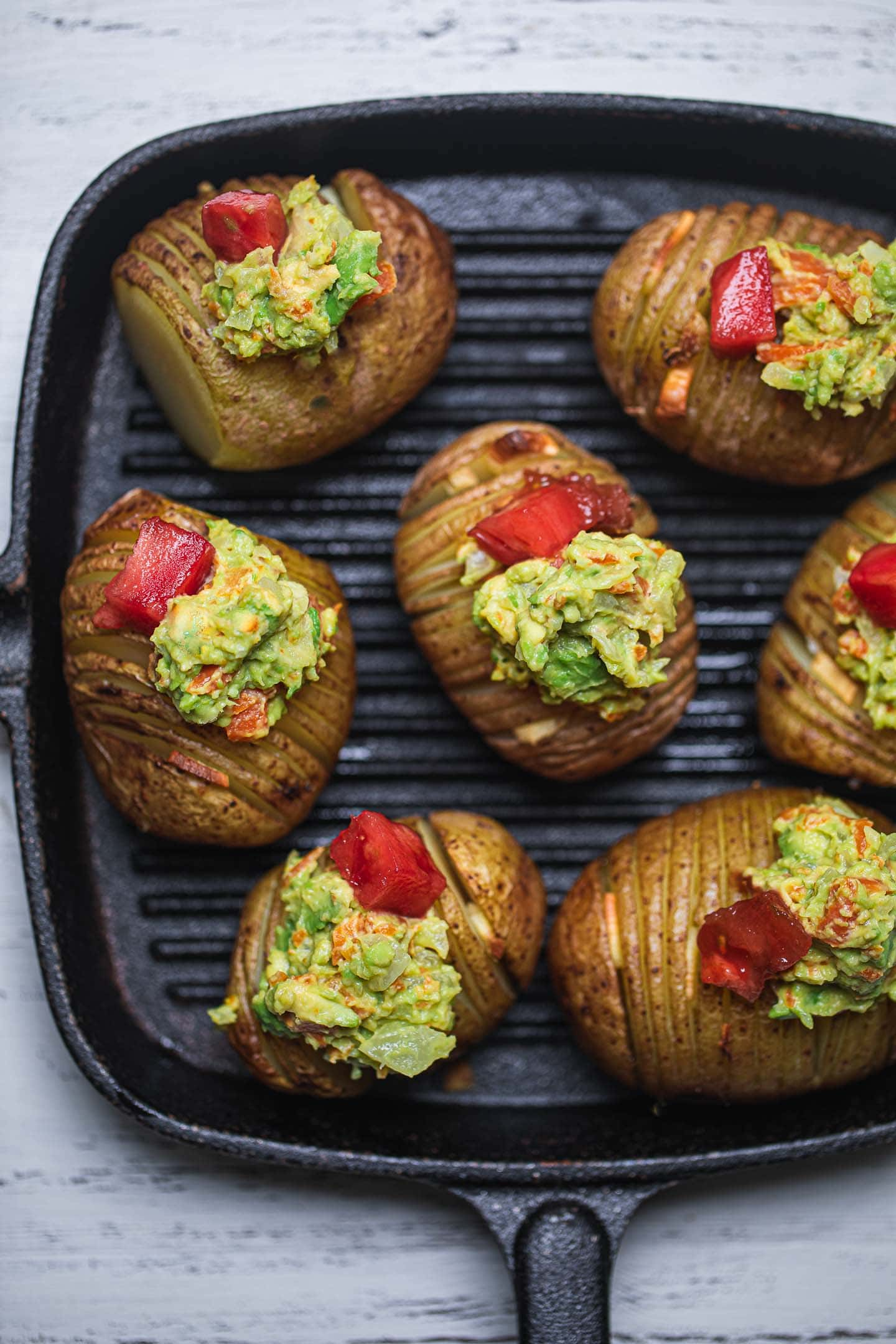 Garlic hasselback potatoes with avocado sauce in a skillet