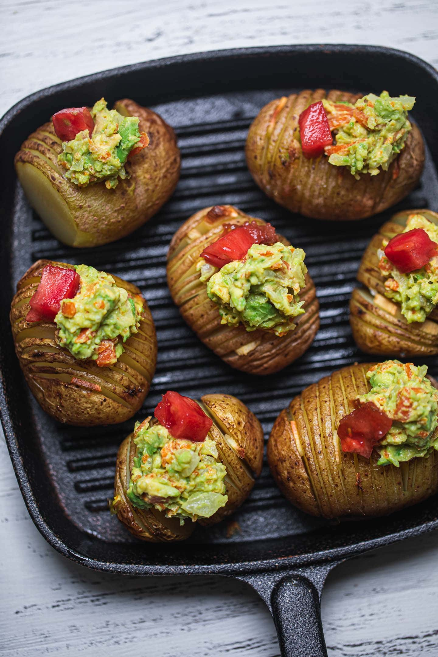 Hasselback potatoes on a skillet with mashed avocado and tomatoes