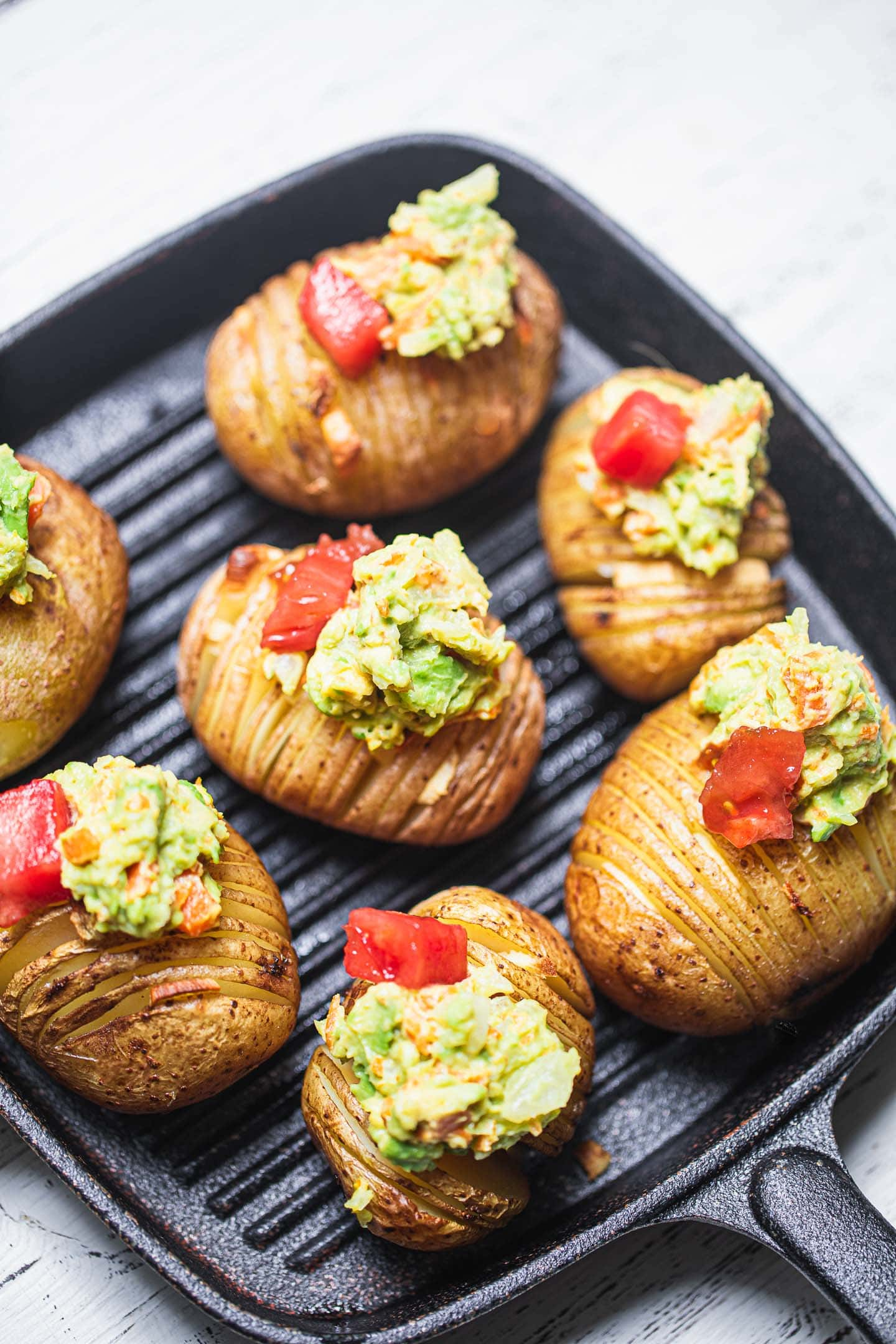 Skillet with hasselback potatoes and avocado sauce
