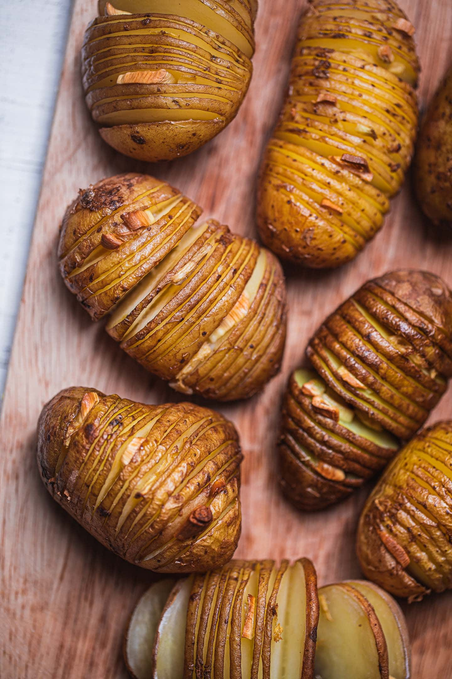 Hasselback potatoes on a wooden board with garlic and ginger