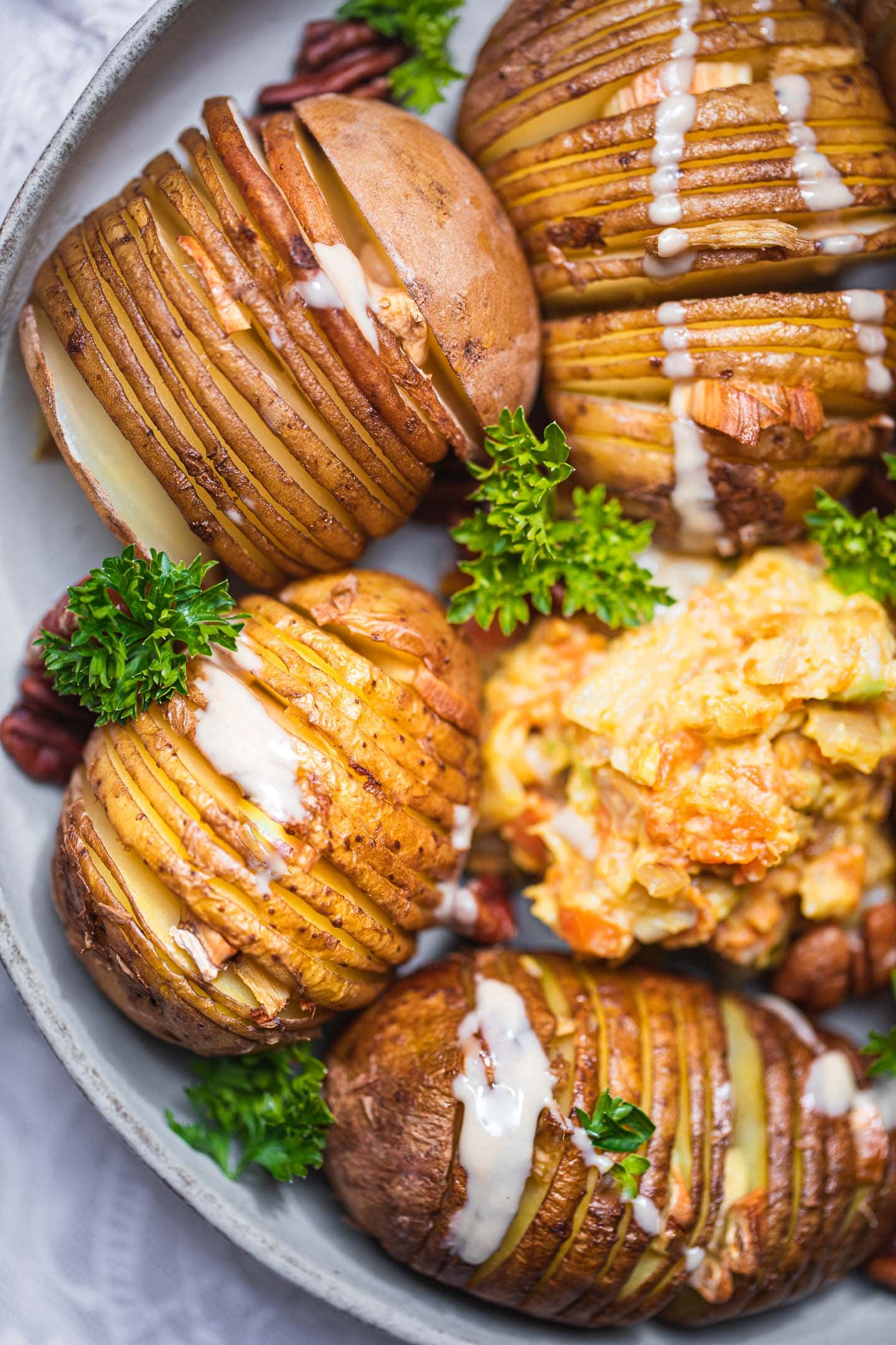 Hasselback potatoes on a plate with avocado sauce