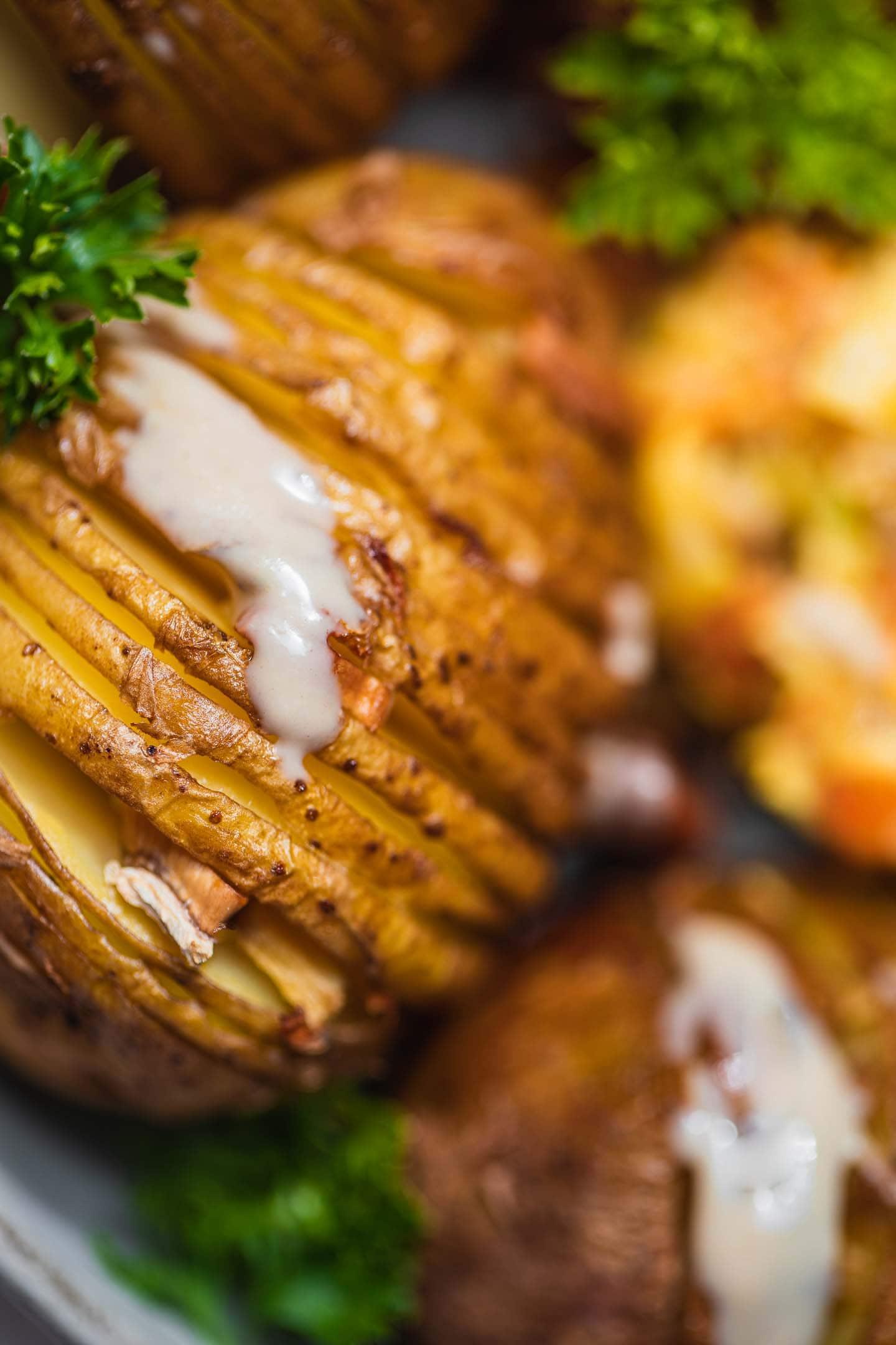 Vegan hasselback potatoes with avocado saucee
