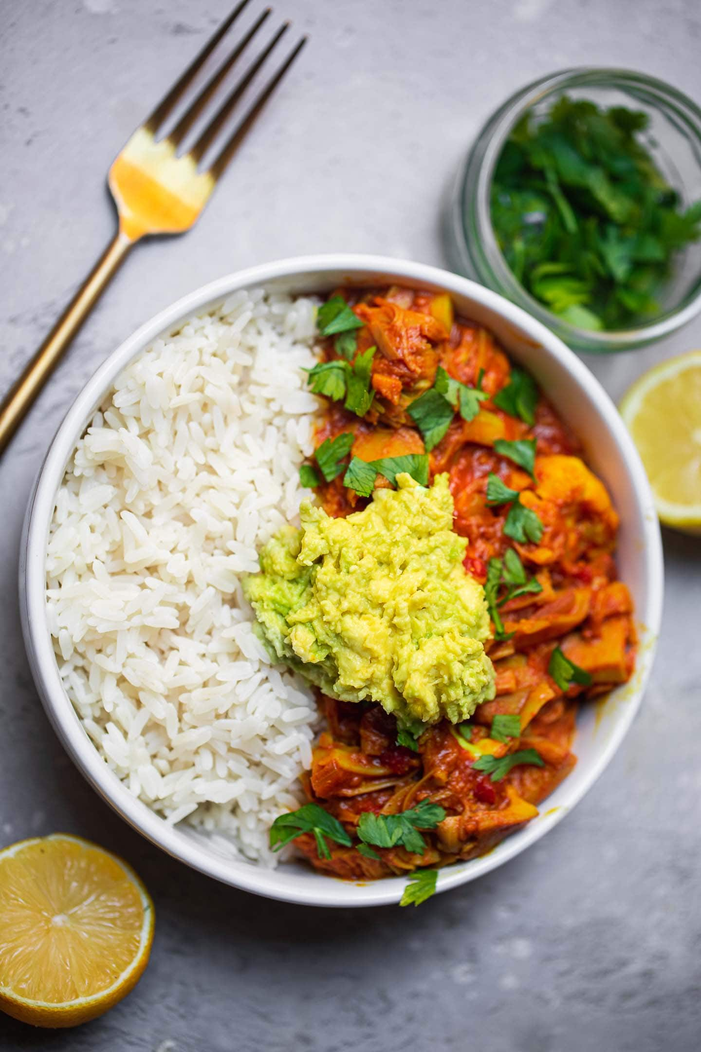 Vegan jackfruit curry in a bowl with rice and avocado
