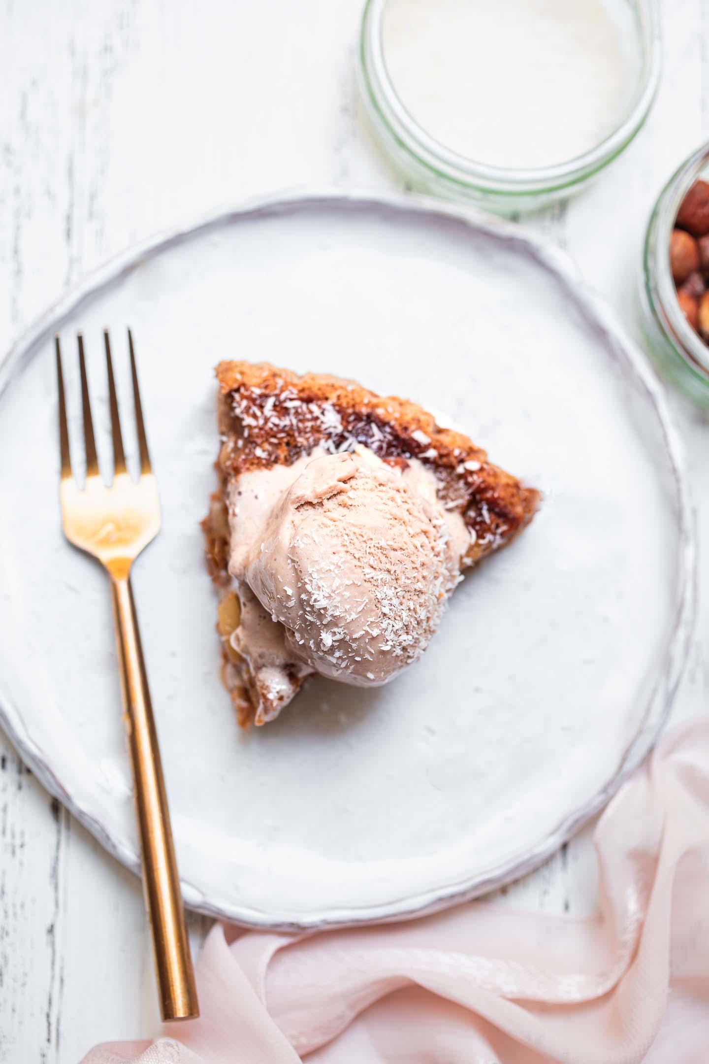 Gluten-free vegan cake slice with dairy-free ice cream on a plate