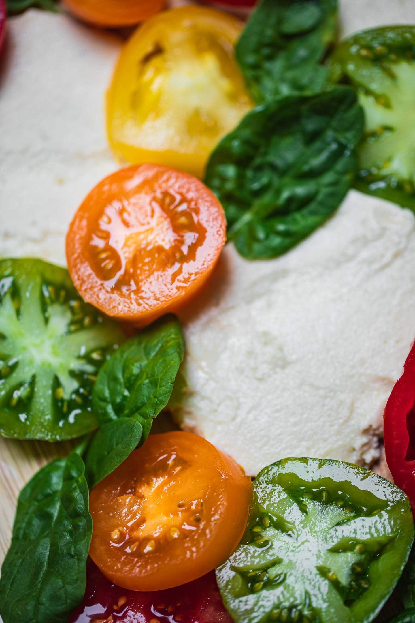 Closeup of a vegan caprese salad on a wooden board
