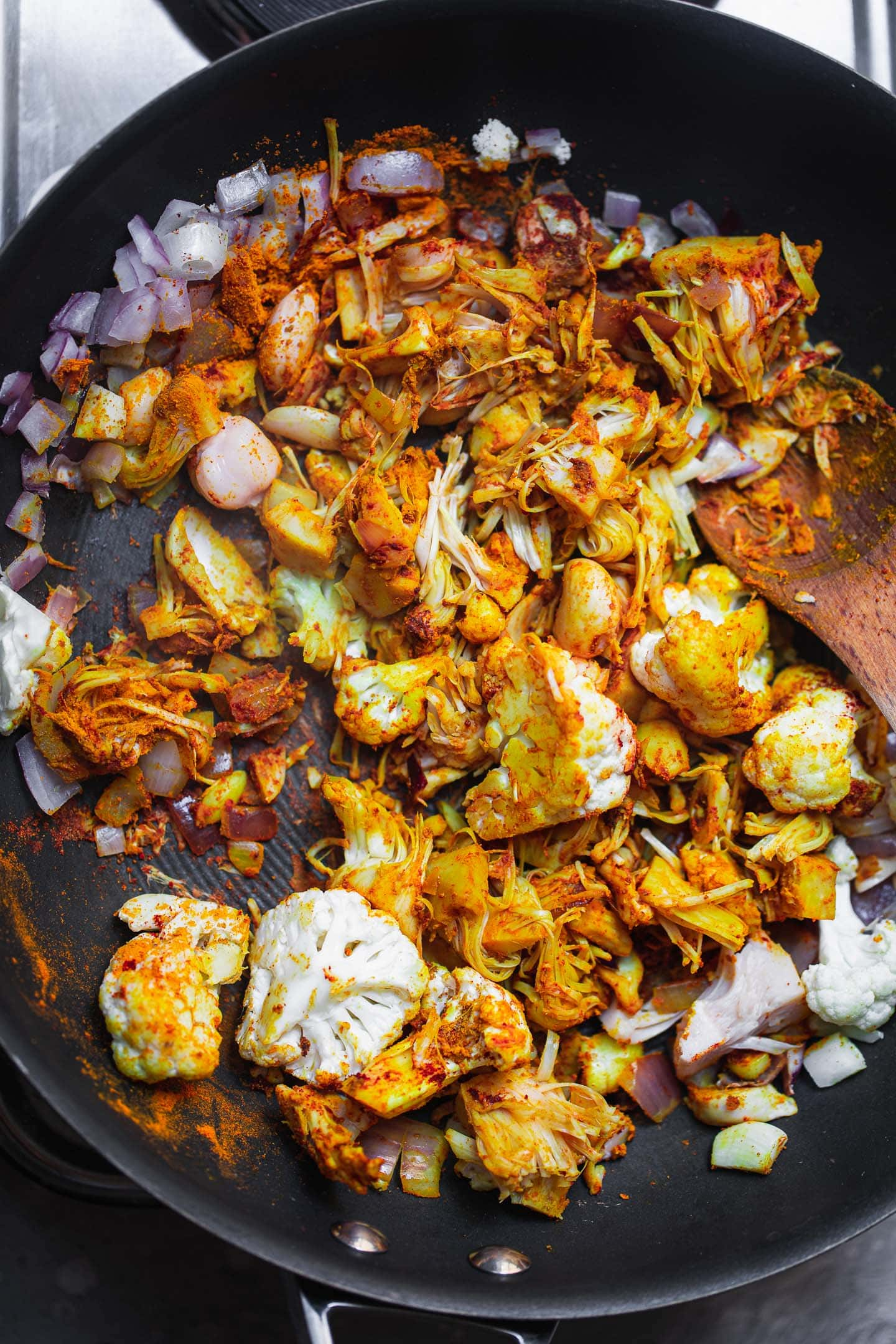 Vegetables and jackfruit in a frying pan with spices