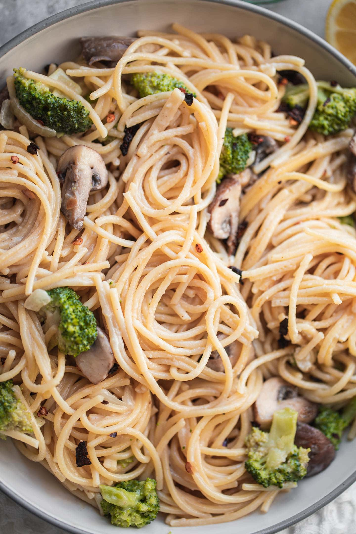 Closeup of a bowl of gluten-free pasta with broccoli and a coconut sauce