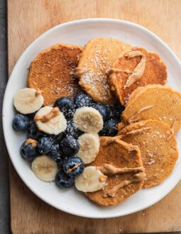 Pumpkin pancakes on a plate with fruit and almond butter