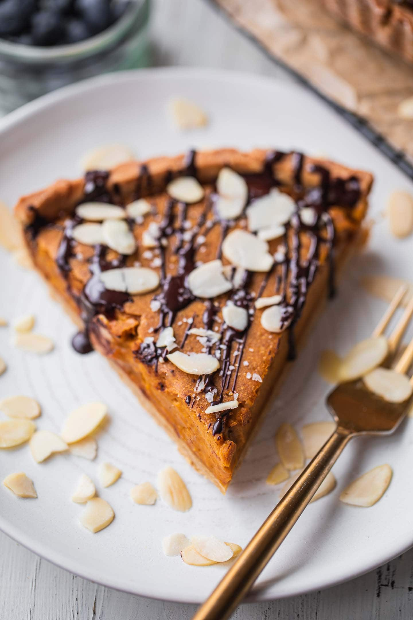 Pumpkin pie with a chocolate drizzle on a plate