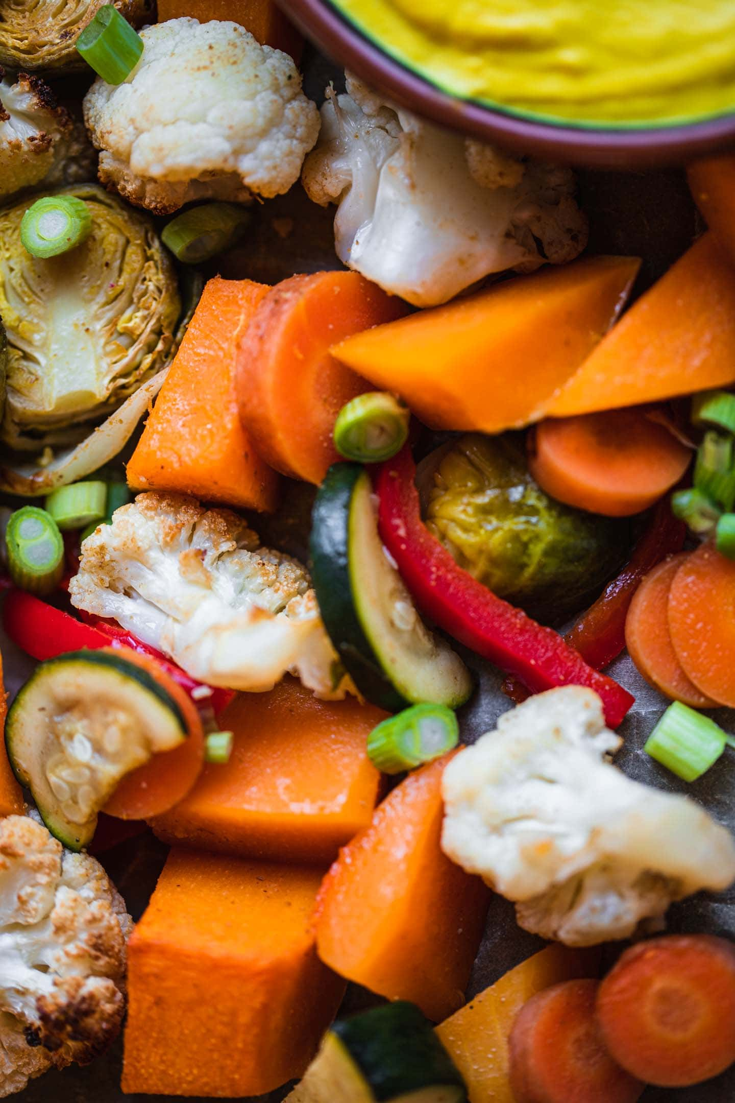 Closeup of Brussels sprouts, butternut squash, cauliflower, carrots, red bell peppers and zucchini on a baking tray