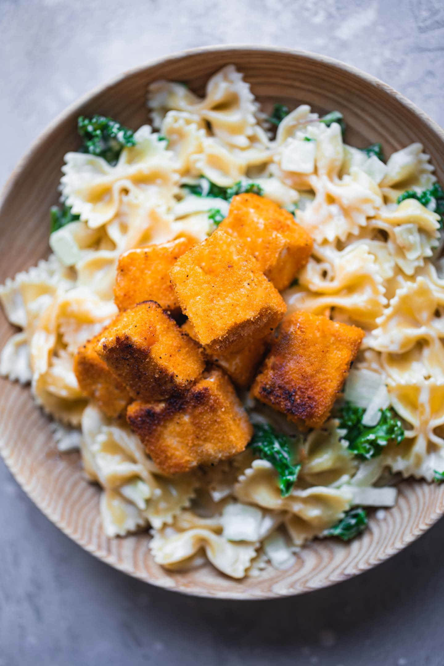 Fried tofu cubes over a bowl of pasta