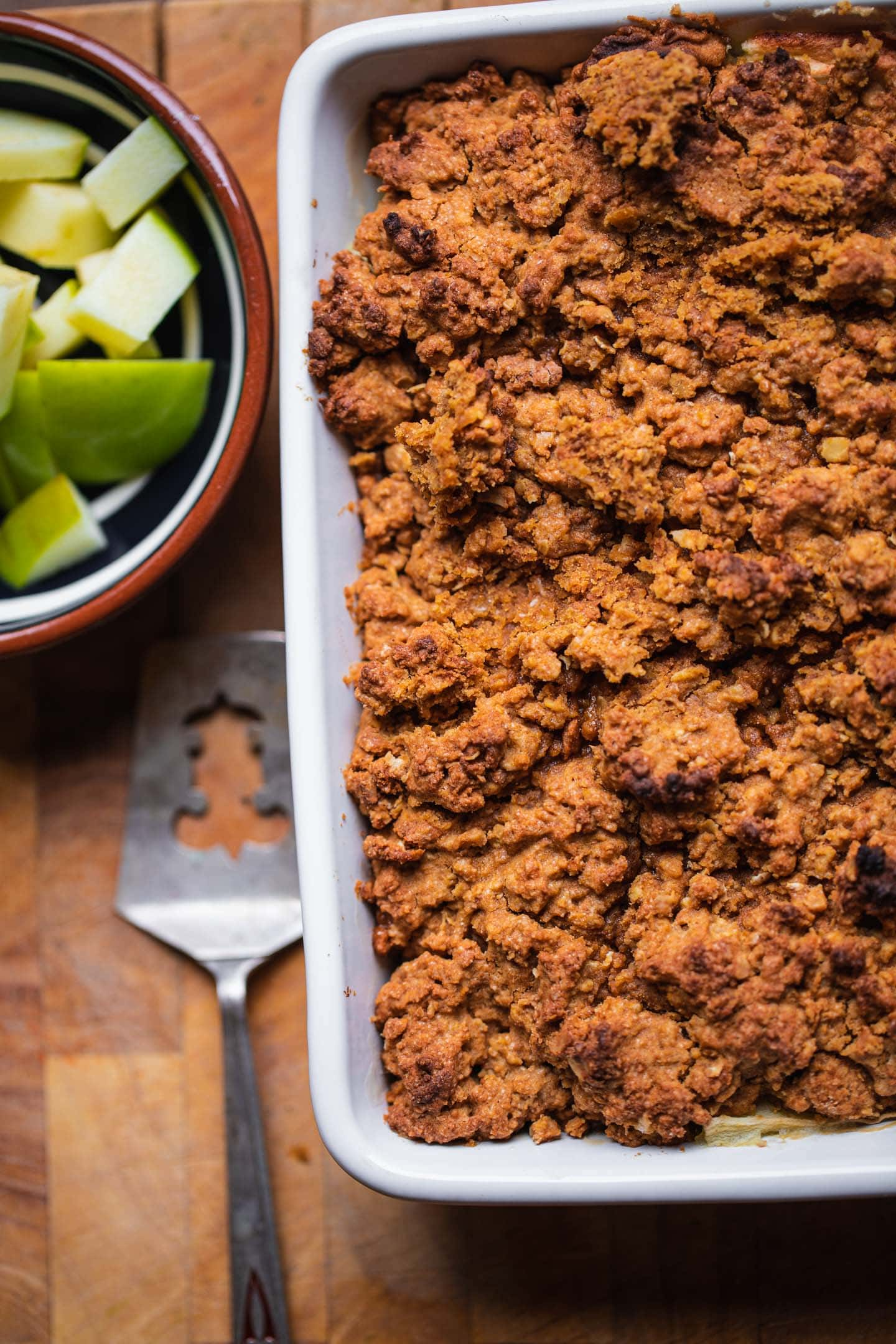 Vegan apple crisp on a wooden board with apples on the side