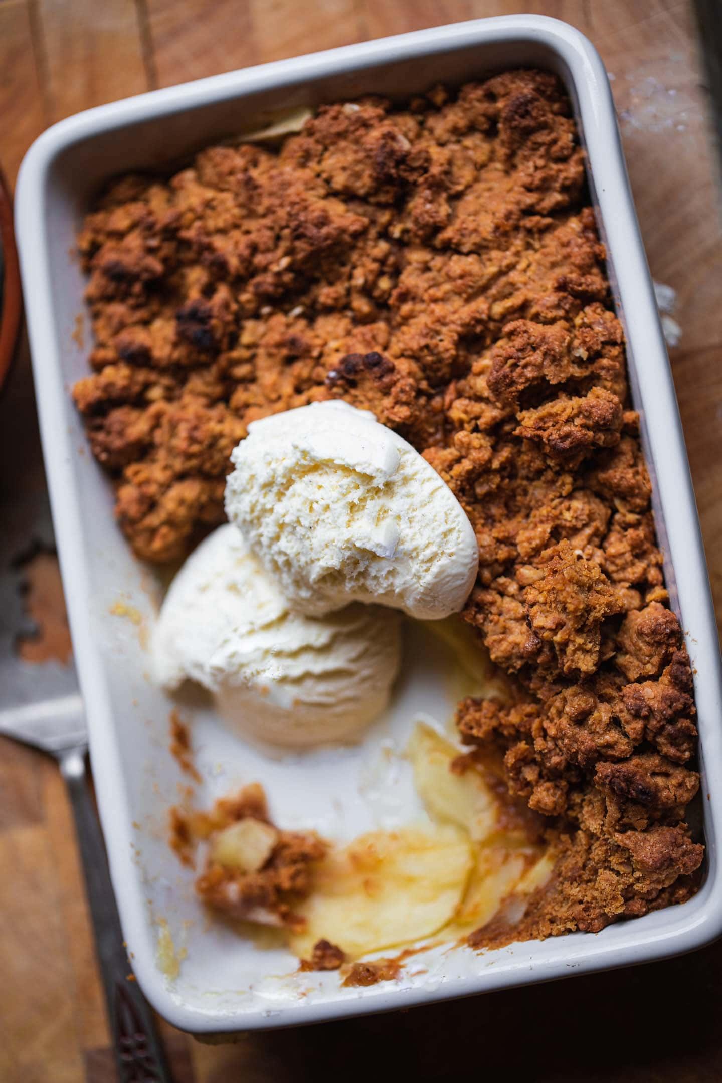 Vegan apple crisp with dairy-free ice cream in a baking dish