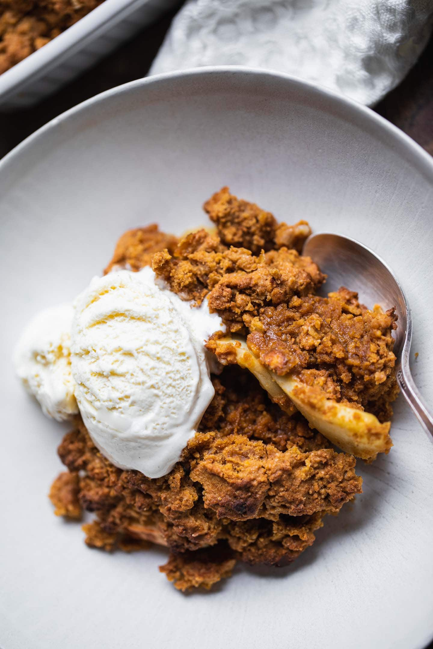 Vegan apple crumble in a bowl with dairy-free ice cream
