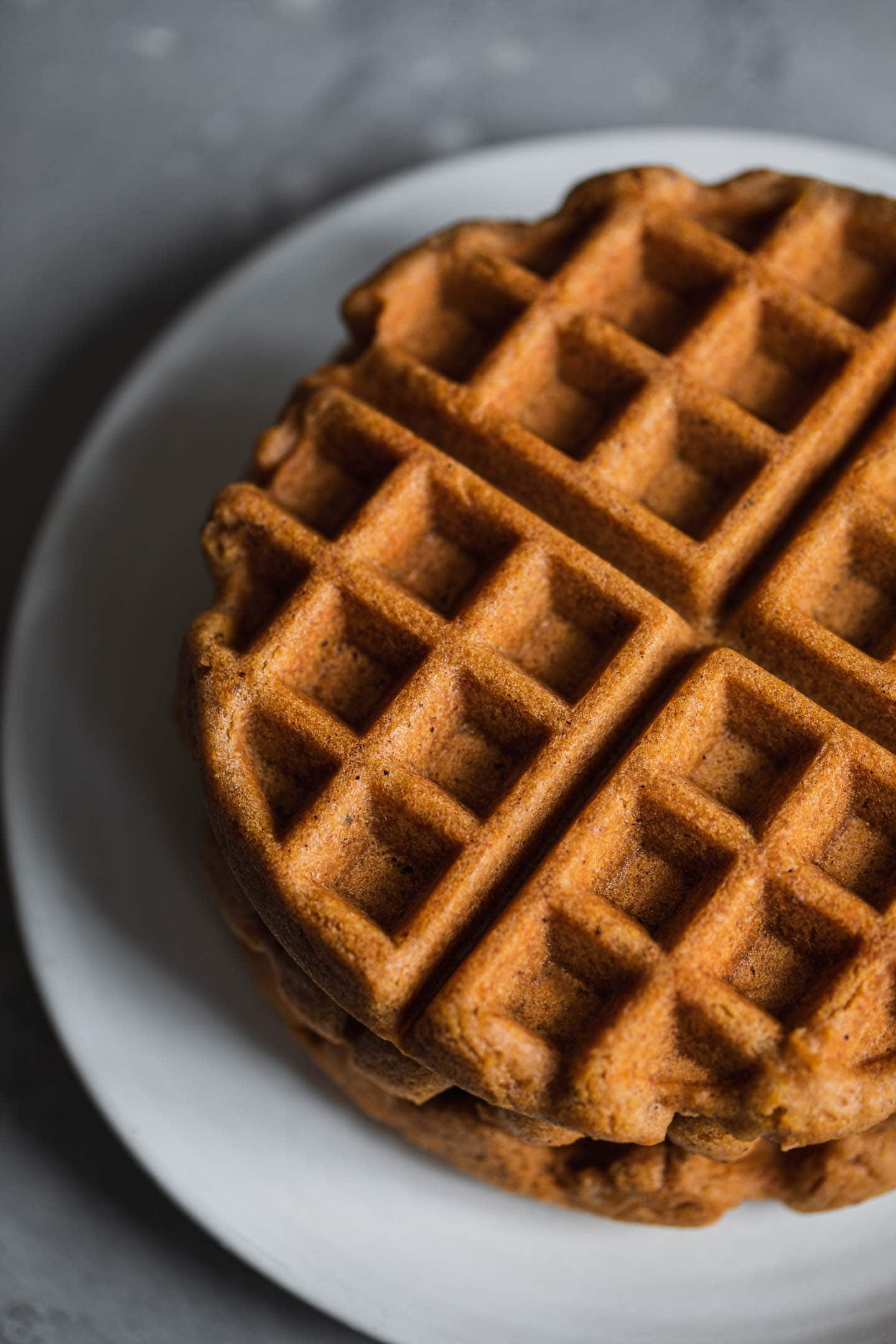 Gingerbread waffles stacked on a plate