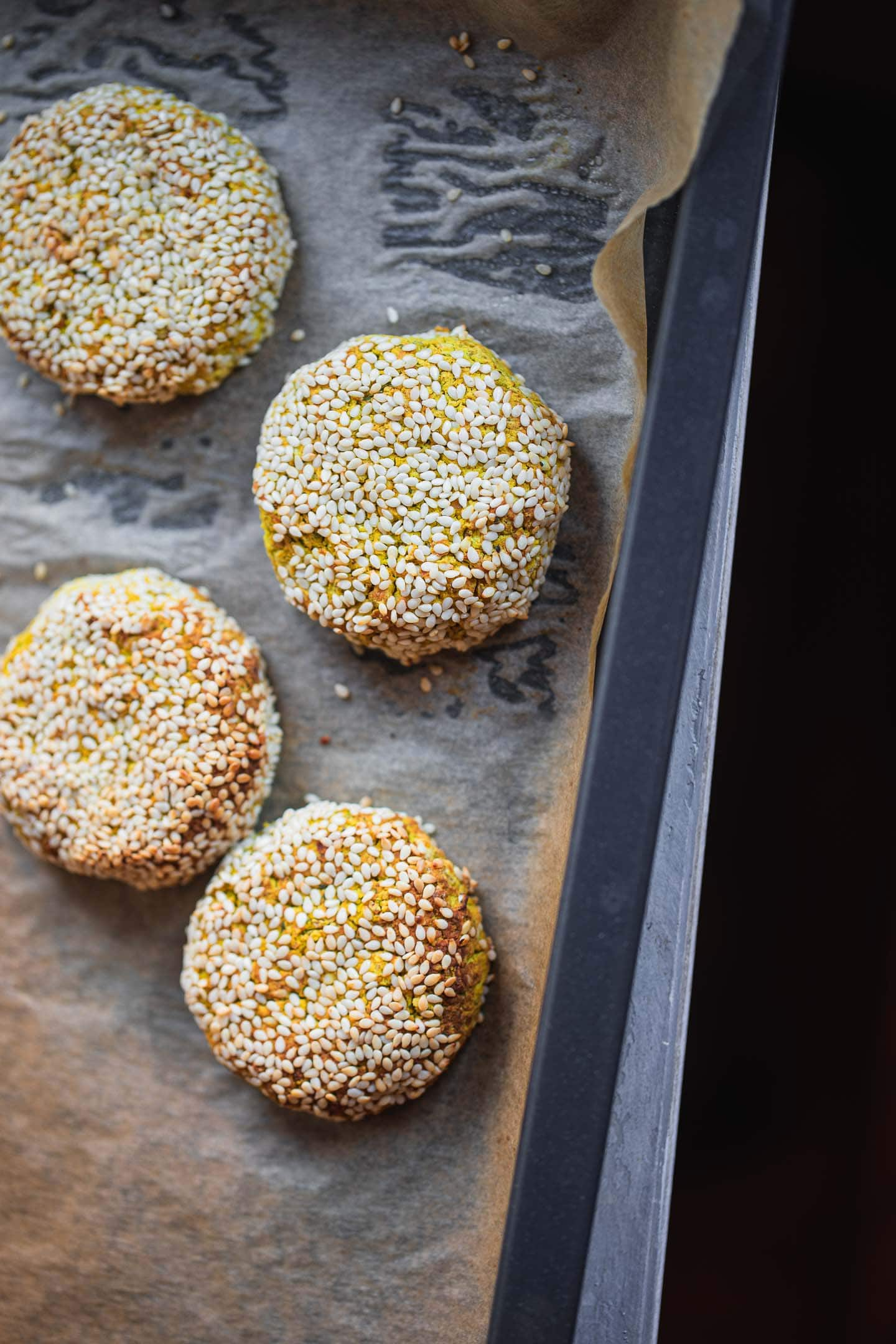 Gluten-free falafel with sesame seeds on a baking tray