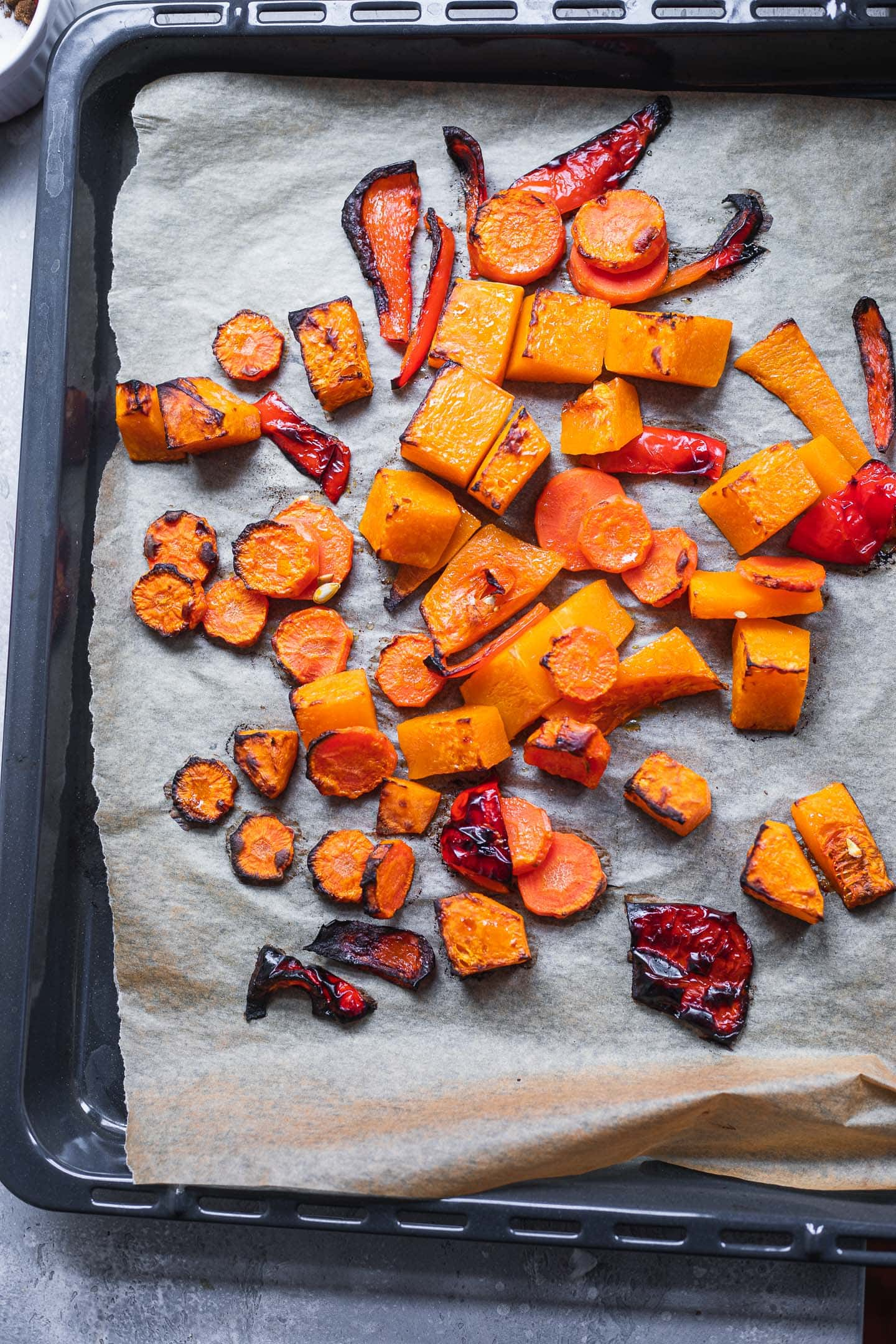Roasted butternut squash, carrots and bell pepper on a baking tray