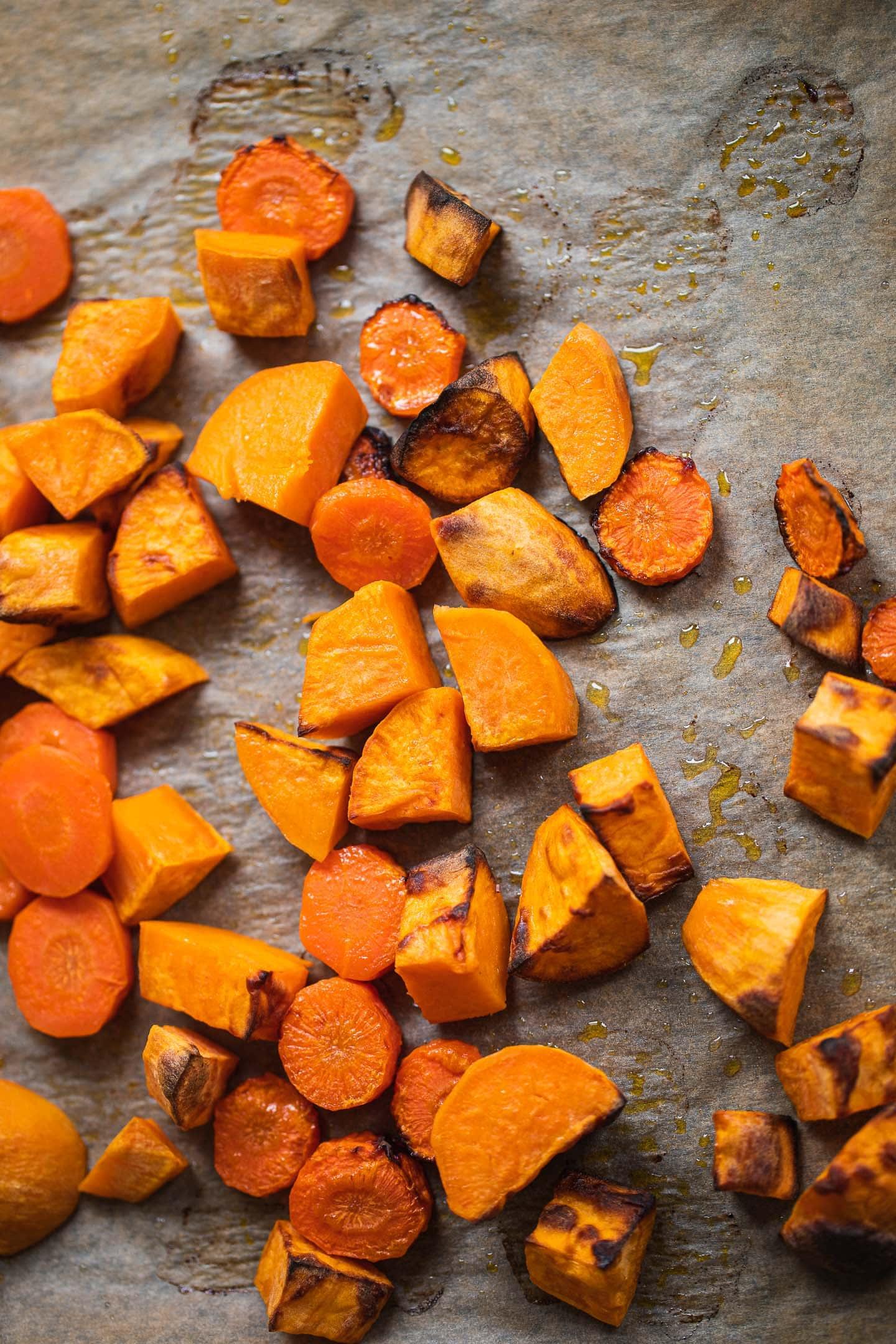 Roasted sweet potato and carrots on a baking tray