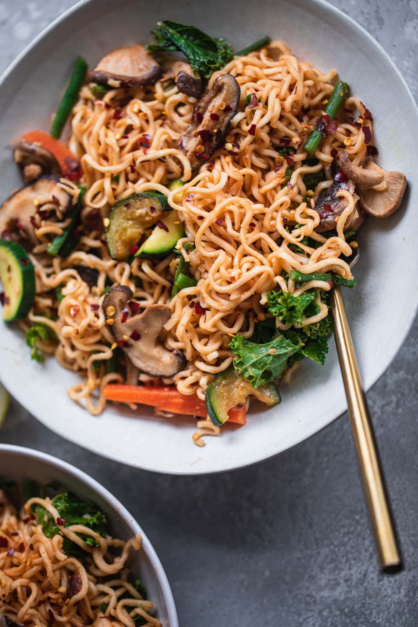 Two bowls of peanut butter noodles with vegetables