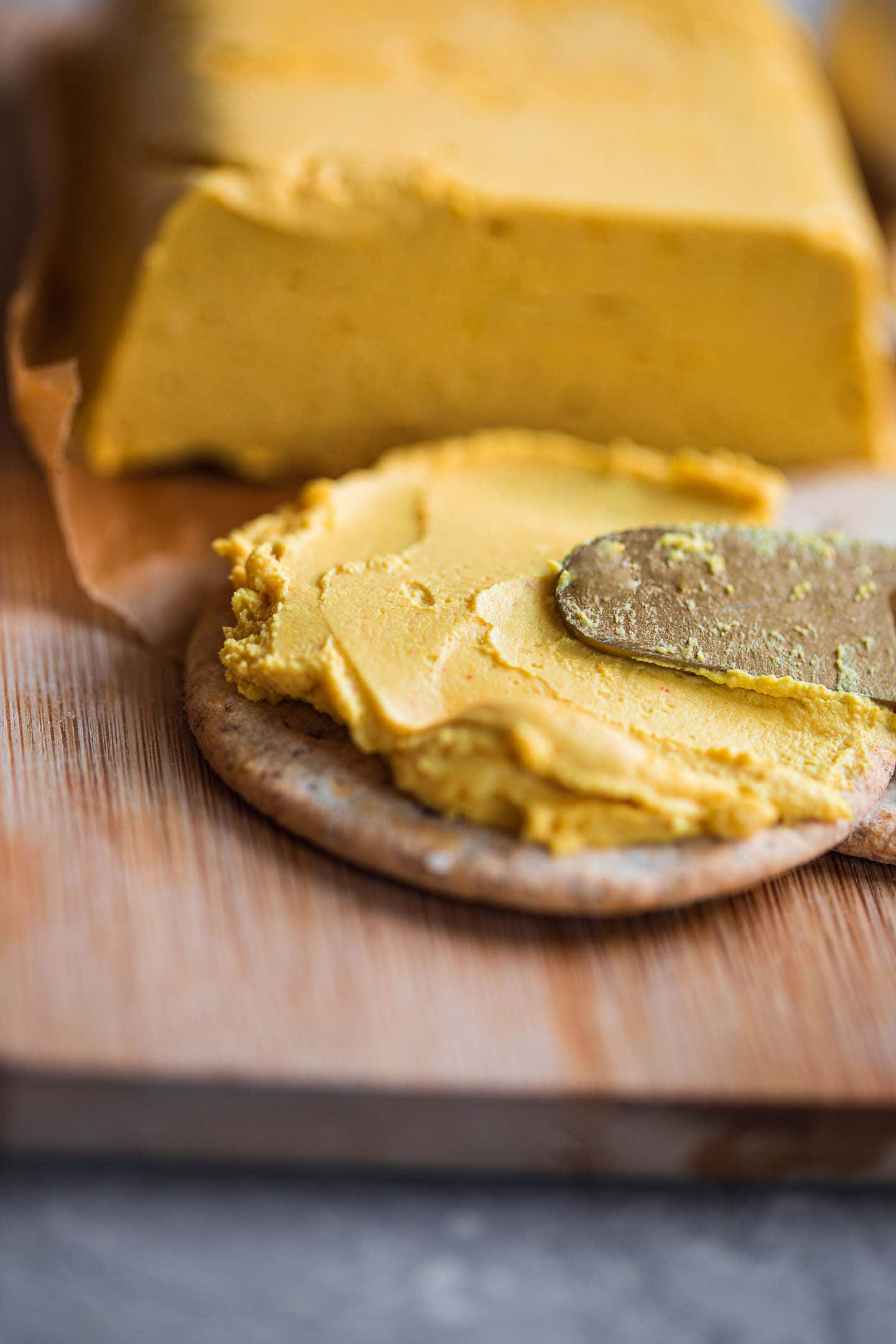 Vegan cheese being spread on a cracker