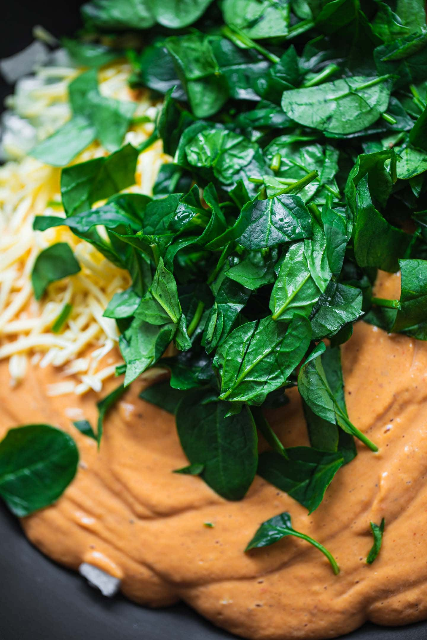 Vegetable pasta sauce and spinach in a pan