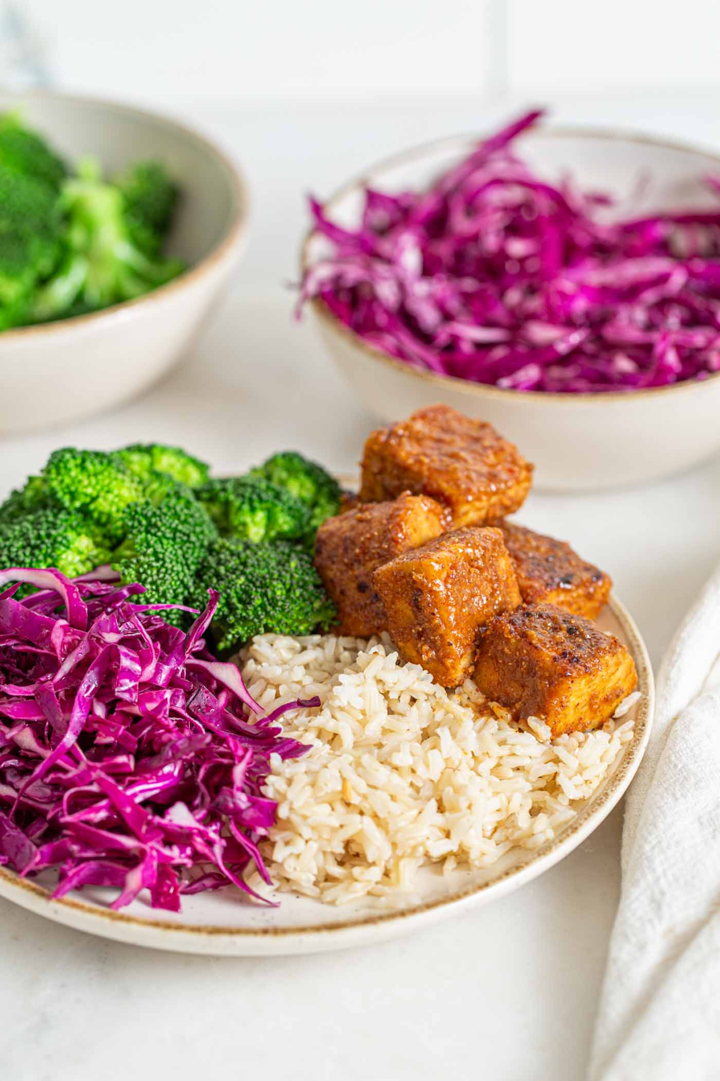 Baked tempeh brown rice bowl with red cabbage and broccoli